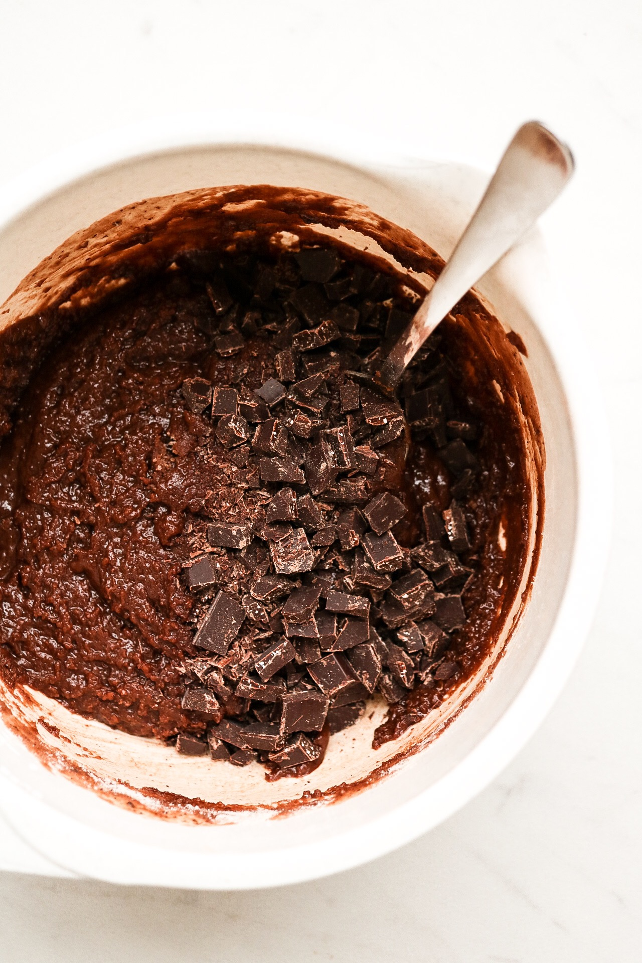 Fold in your chopped chocolate into the batter and mix! Then, just pop em into the oven for about 15 minutes.