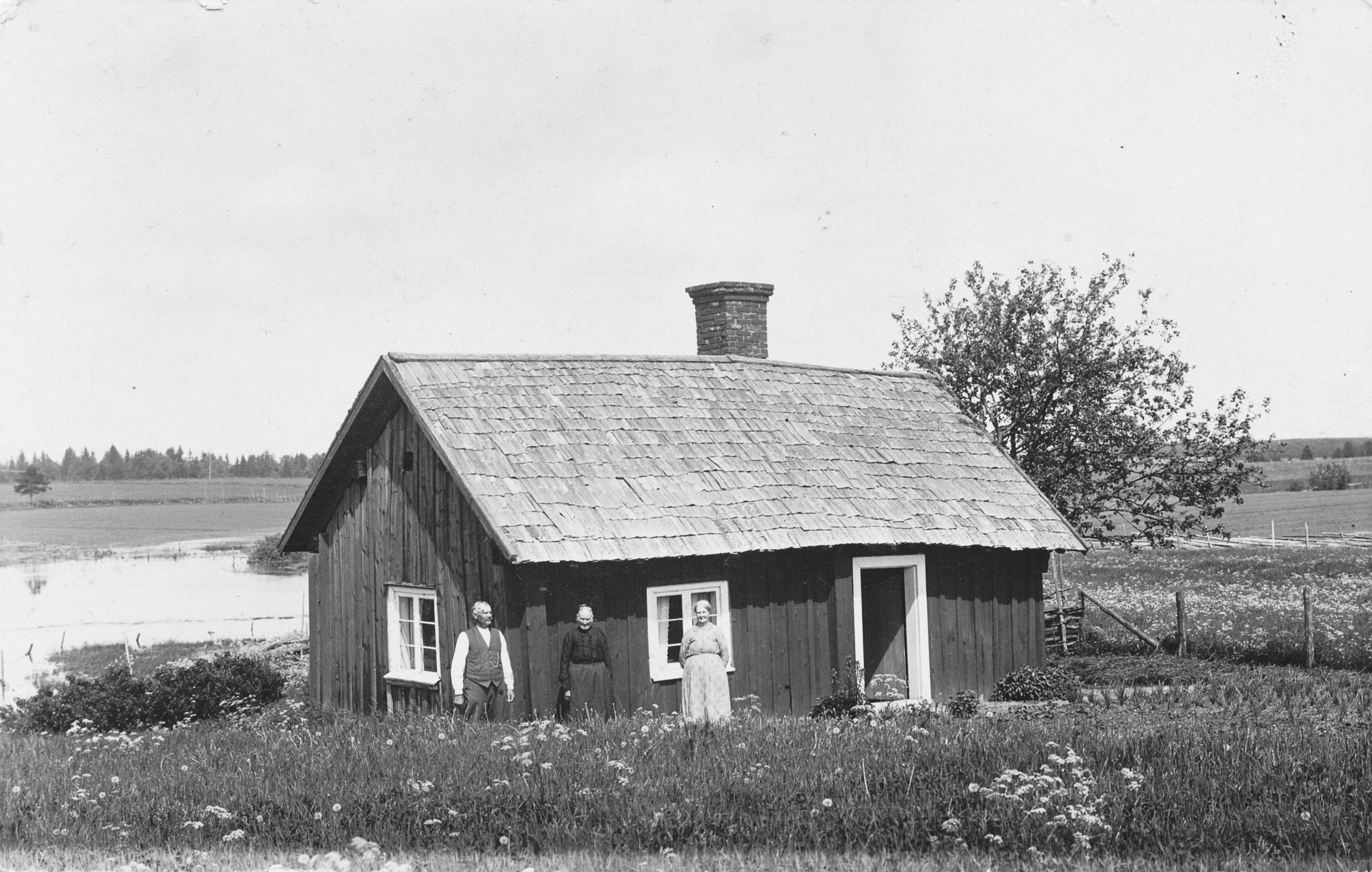 Brobackens backstuga på ofri jord väster om Kivenäbben. Djuran i bakgrunden. I mitten änkan Anna-Stina Bergkvist. Övriga okända.