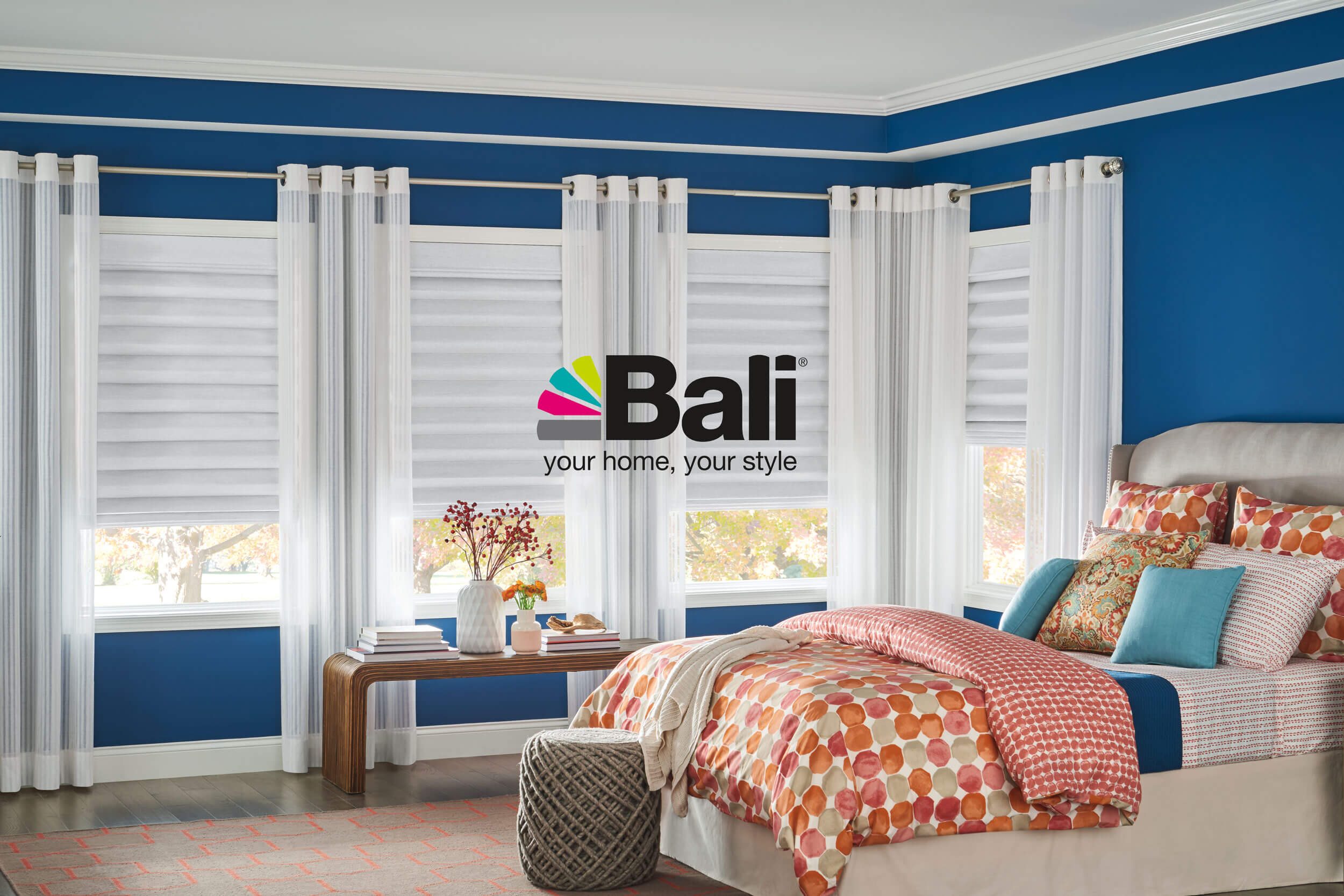 Bali Roman Shades and Drapery in a bedroom, with the Bali logo overlaid