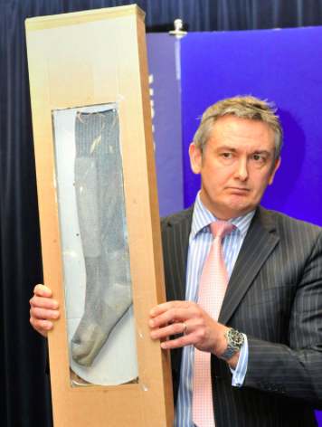 Detective Chief Inspector Phil Jones holds up a sock similar to the missing one