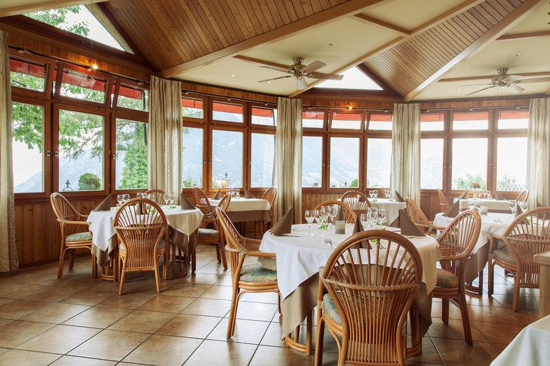 La Véranda - Salle à manger principale de notre établissement : des tables classes et espacées au milieu d'une véranda donnant sur un panorama spectaculaire sur la région.