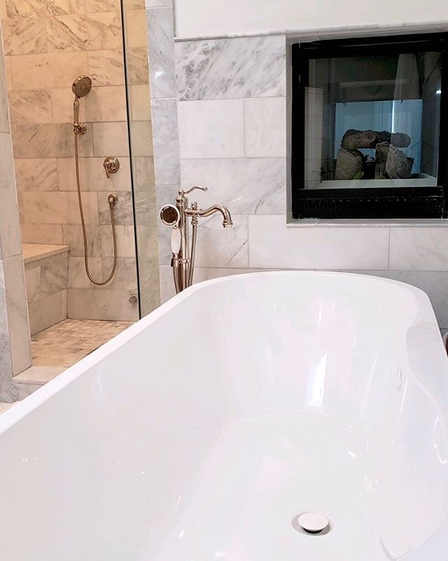 One of our latest luxury master bathrooms is complete with a fireplace that sits over the soaker tub, and is visible and accessible from the master bedroom as well! What do you think?  ___ #chicagoluxury #chicagocontractor #homeimprovement #fixerupper #windycityrehab #fliporflop #chicagorealtor #chicagobusiness #luxuryhome #masterbath #bathroomrenovation #fireplace