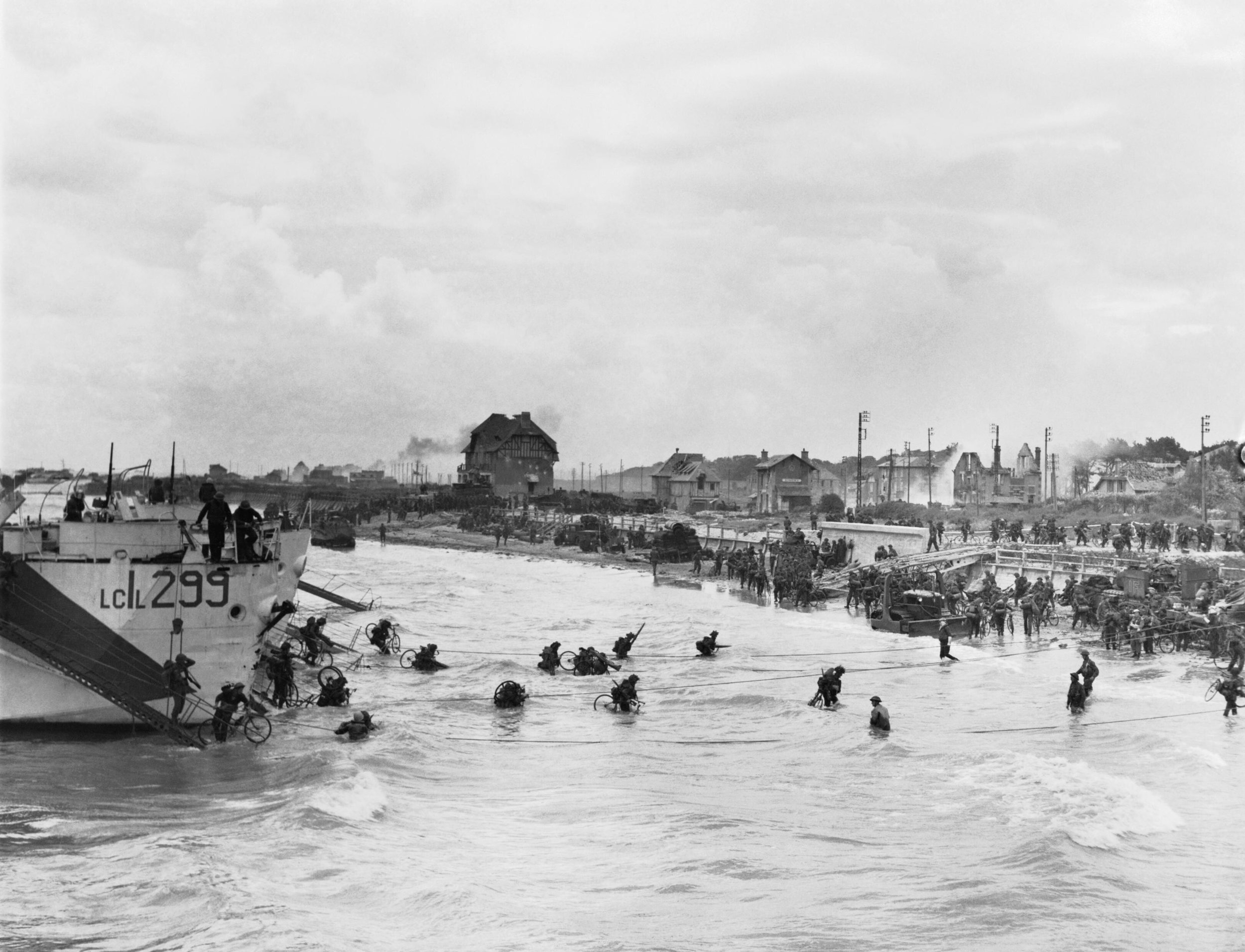 Follow-up waves of the 9th Canadian Infantry Brigade disembarking with bicycles from landing craft onto 'Nan White' sector of Juno Beach at Bernieres-sur-Mer, 6 June 1944