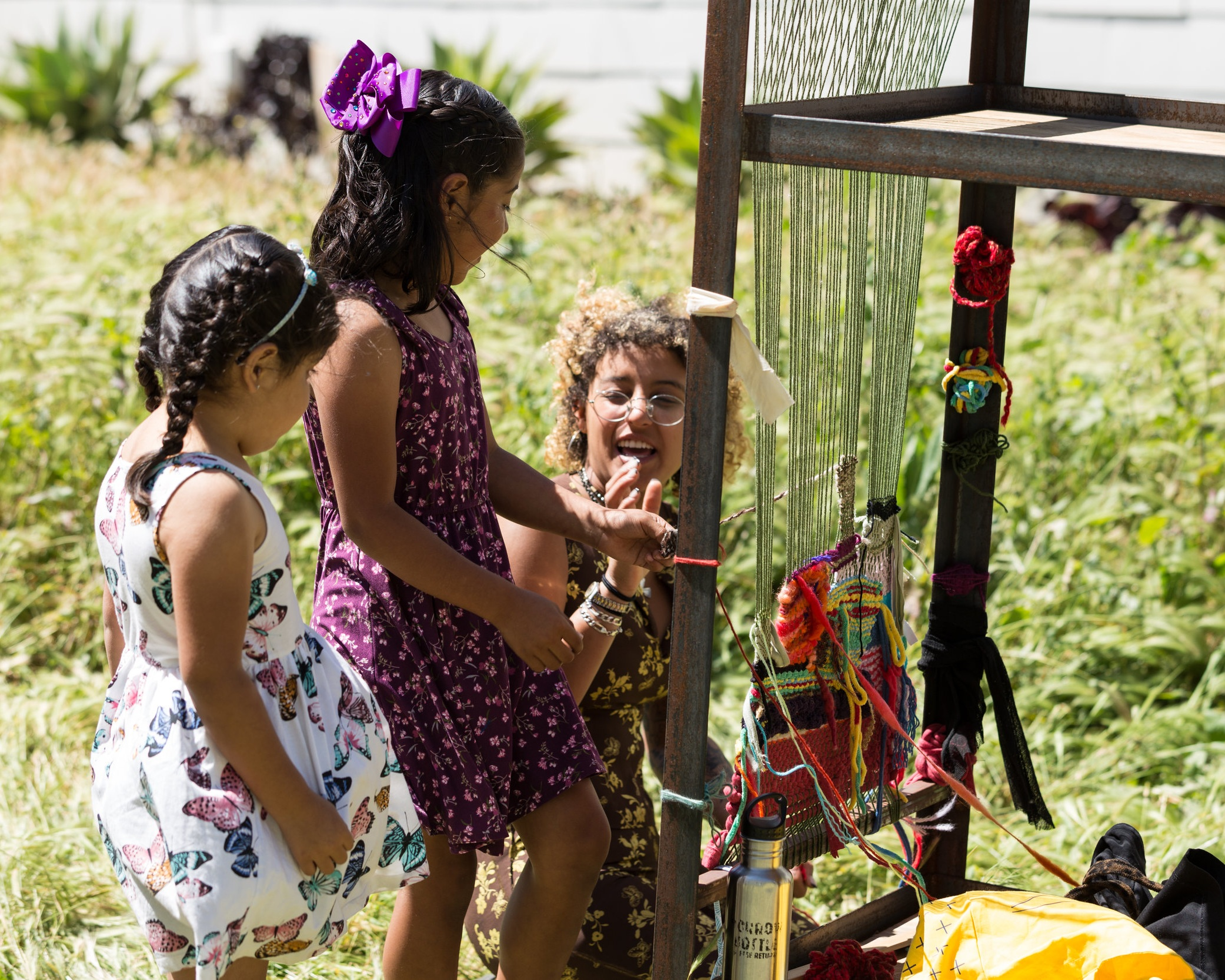 children interactive with loom installation at opening for  Ganas de Existir!  in San Pedro, CA 2019