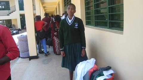Aline in school uniform and waiting for room assignment.