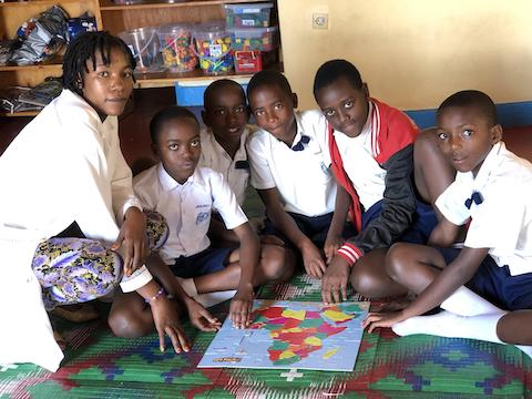 Social studies teacher Tricelle and her students enjoy textbooks and puzzles provided for her class.