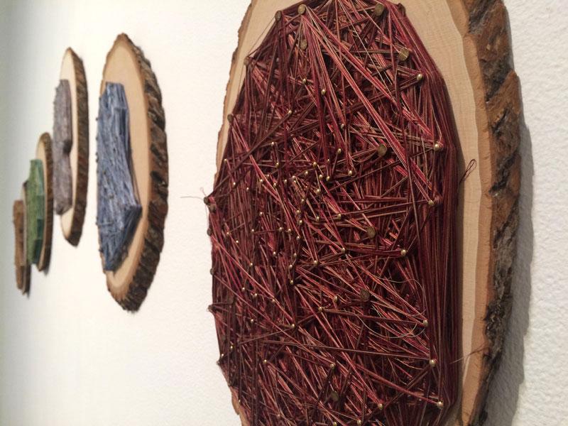 """Obligatory Kin. 72""""W x 18""""H. Log Slices, Nails, Thread. (2014)"""