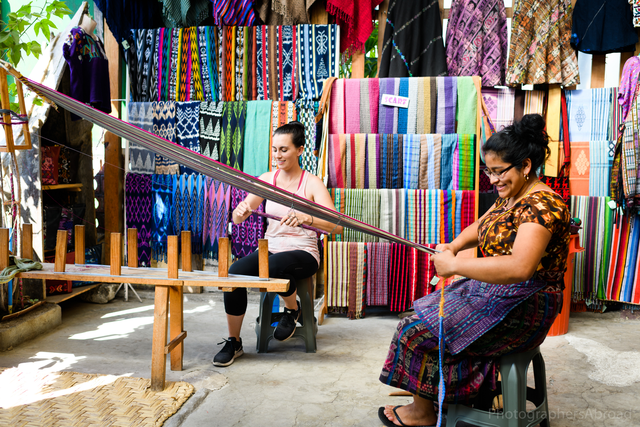 I wind threads around the shuttle - a large wooden dowel that passes the thread through the layers of the yarn - while Ana Lady sets up the backstrap loom.