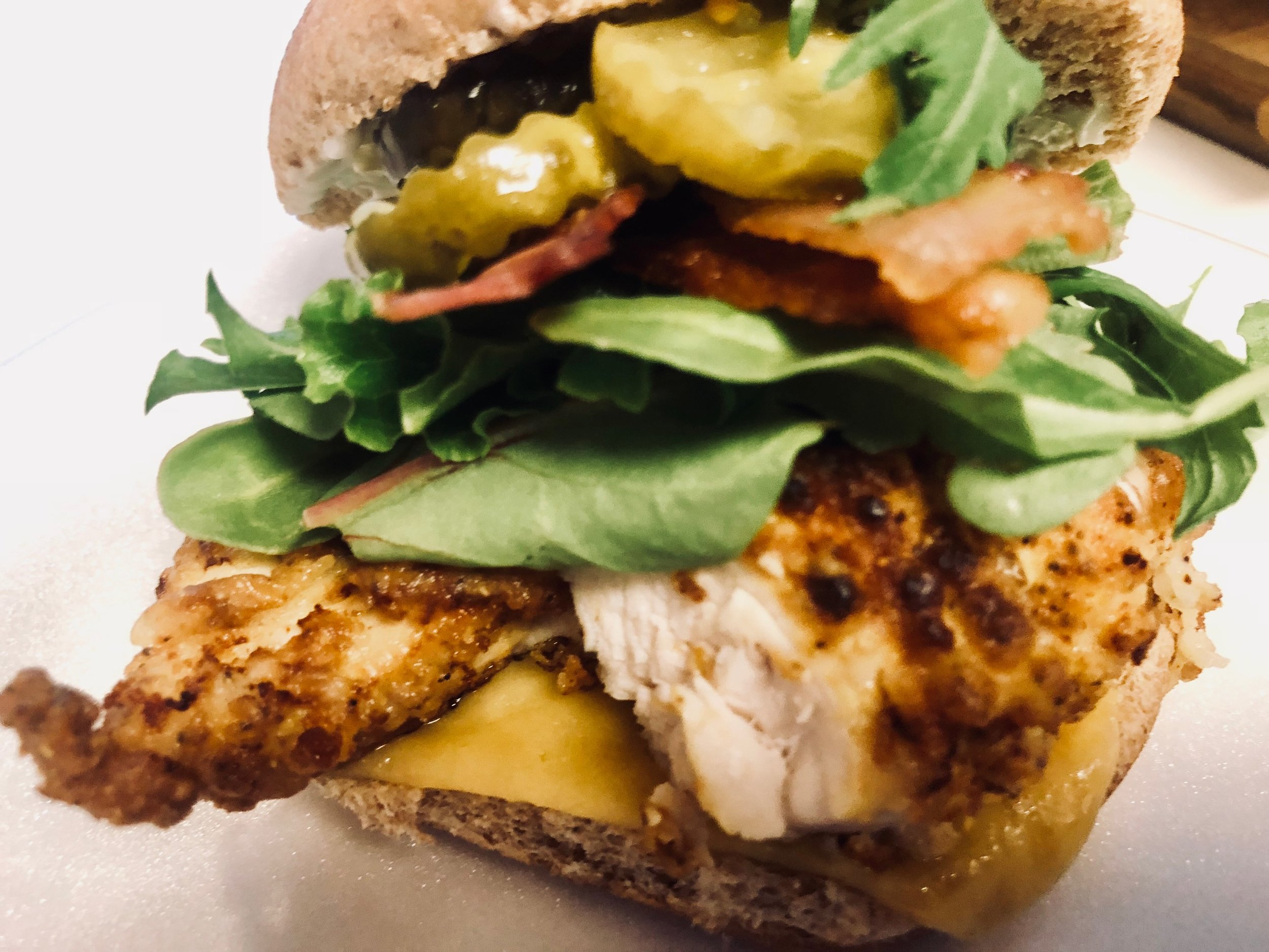 Fried chicken breast seasoned with Chef Monica's NC Red Spice, topped with arugula lettuce, thick cut apple bacon, tangy sweet pickles with an aioli spread, American Cheese on a fresh wheat bread bun.