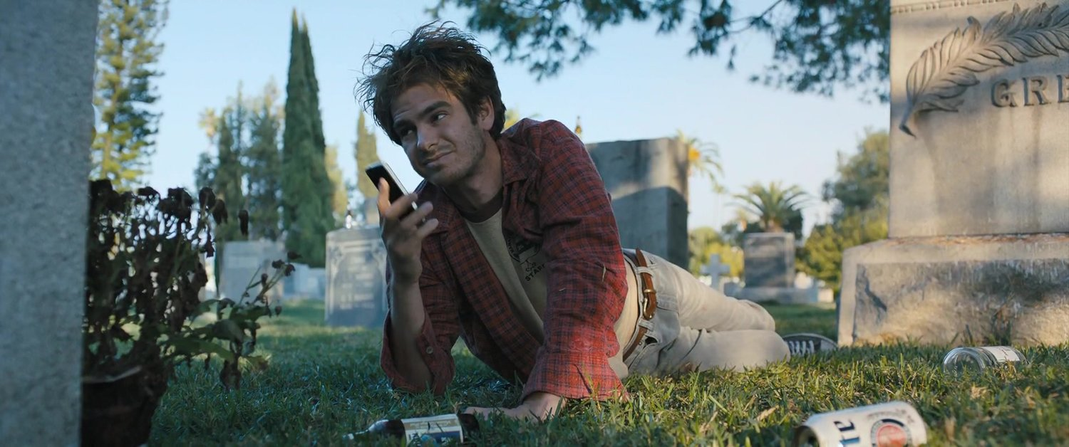 "David Robert Mitchell's  Under the Silver Lake  might be simultaneously the most thought provoking and frustrating film I've seen so far in 2019. While it certainly isn't the film I enjoyed the most (that would be Harmony Korine's lush and hilarious  The Beach Bum ), the film that most viscerally excited me (Gaspar Noe's  Climax ) or the film that left me most stupefied by its utter lack of clarity and cohesion (Jordan Peele's  Us ).  But it is the film that seems to have embedded itself deepest into my thoughts and fantasies after my first viewing of it. Mitchell, who is previously known for the equally seductive, stylish and mostly disappointing horror film  It Follows , appears to be an artist so deeply invested in theory and logical ideas that he often fails to match his fascinations in narrative cohesion.  The film, which follows the scrappy, unemployed and potentially sociopathic Sam (played by Andrew Garfield) and seeks to unravel a mystery pertaining to a disappeared woman, presents a Los Angeles that is totally awash in slogans, messages, and maybe even clues that ultimately lead nowhere.  Under the Silver Lake  could be viewed in the context of Baudrillard's fourth stage of pure simulacra. While the world is full of information, Mitchell suggests, it is utterly devoid of coherent meaning.  Garfield's Sam is, like the fictional Los Angeles mystery solvers that came before him, a pure encapsulation of his time period's conception of masculinity. Just like Raymond Chandler's Phillip Mawlowe was the image of stoic, grizzled 1940s war veteran taciturn or Thomas Pynchon's Doc Sportello was an embodiment of early '1970s adrift and stoned out paranoia, Sam is a manifestation of 2010s, post-digital, late stage capital confusion, boredom, and ineffectuality. He is jobless and seemingly totally indifferent towards the fact that he is about to lose his apartment. His deep knowledge of rock n' roll music and film noir history are skills that have no tenable place in the labor economy. It's hard not to imagine Sam reading Jordan Peterson without a shred of irony, and posting paranoiac thoughts on one of 4chan's many alt-right pages (LA slacker division, perhaps).  Mitchell himself has conceded that Sam is very much an avatar for the treacheries of late capitalism, and the attendant male rage that brews when you are led to believe your whole life that you are entitled to success, a life, and an identity, only to find a world in which wealth is only attained by those who already have had it for generations. Like Walter White, Sam is indoctrinated in late stage capitalism thinking that says being a man means being a provider, or at least, a rich guy. Unlike Walter White, who at least fueled his intelligence and narcissism into a lucrative criminal enterprise, Sam has given up on everything other than slacking and conspiracy obsessing. ""Sam could continue reaching for things,"" said Mitchell, ""But he's thinking,  what's the point?  Even being able to buy a house, for our generation, is like a near-impossible task. So how do you process that? Maybe you go looking for meaning in strange places.""  Though better at seducing women than we are initially lead to believe, Sam's psychological profile is primarily defined by boredom and confusion punctuated by the occasional outburst of hyper-violence (25 minutes into the film, we see Sam savagely beat young boys for the rather innocuous childhood crime of egging his Ford Mustang, which he loses shortly after in an asset seizure for failing to make payments, a powerful metaphor for capitalism's decimation of the American dream).  The mystery kicks into gear when the girl (played by an uncharacteristically bubbly but thoroughly characteristically enigmatic Riley Keough) that lives in the same Silverlake complex and whom Sam almost sleeps with suddenly disappears before being found as one of the three female bodies found along with the body of a local billionaire. Sam then drifts through the seductively photographed Angeleno landscape where we meet his odd-ball friends and the beautiful girls that tempt him.  Nevertheless, the mystery doesn't drive the plot as noticeably as the indecipherable enigmas populating the images seem to halt that very mystery in its tracks, and Mitchell continuously distracts by populating the the film with red herrings and images of dubious fascination. Again one could draw thematic comparisons with both Pynchon's  Inherent Vice  as well as its PT Anderson cinematic adaptation in that  Under the Silver Lake  is a Los Angeles set film noir mystery thriller that meanders and pontificates vastly more than it thrills.  Garfield's Sam has found himself in a world that bewilders and has ceased to make sense to him. He sees codes and messages everywhere. But like most conspiracy nuts, Sam's proclaimed knowledge of the world below, his penchant for identifying conspiracy, is really a survival mechanism (research by the psychologist Jan-Willem van Prooijen suggests that unstable self-esteem and control issues are the primary traits of conspiracy theorists), or even worse, a delusional distraction. Sam is off, he seems like he could have PTSD, and his quest for the truth comes off as little more than a flaccid attempt to gain control in an environment that is hostile and unknowable towards him.  In late capitalism, advertising has become an omnipresent, malevolent force. Sam wants to believe that there is deeper meaning in these messages, but meaning eludes him all the more the deeper he gets in his decoding of the mystery.  I found Sam's age to be relevant here: 33. Sam is an early millennial or late Gen Xer. The codes of sexuality and expression of the millennials he comes into contact with in the film are utterly alien to him. I am 31, and found this to be perhaps the most resonant idea in the movie. I remember a time when the Internet was discussed in Utopian terms: that the accessibility of information would free us. What has proven to be the reality of the post-digital revolution? The more malignant cultural idiom is that, instead of wider access to information allowing the population to be more well-informed and govern itself according to these objective truths, humans tend to use digital information to further curate their own ideologies, inoculating themselves from information that clashes with their own narratives, and often using the shield of the Internet (""in the guise of a fiction, the truth about himself is articulated,"" said Zizek on this subject) to revel in the most toxic aspects of their own persona.  The more innocuous but no less culturally stressful phenomenon is the anxiety that develops when constantly trying to keep up with culture's rapid forward momentum. As an artist and cultural critic I do keep up with culture: visual art, books, films and music alike. But there is a flattening of meaning when constantly pressured to experience more, and more, and more culture. The tyranny of the new: new music, new films, new YouTube videos, new products, it's all just products, instantly available and aggressively advertised towards you in both your physical and digital environments. Every Friday on Apple Music, at least five new releases automatically upload into my cloud (if I have already added music by the artists in question in the past). The result? I absorb nothing, I find context in nothing. How can you achieve the kind of passionate fandom that say, hardcore punk rock fans in the 1980s felt, when you don't have enough time to listen to anything more than once? And the fact that all this information is controlled and distributed by a few corporate behemoths further negates meaning in its purest sense. ""We live in a world where there is more and more information, and less and less meaning,"" famously wrote Baudrillard.  In many cases, the mystery that forms the crux of the movie seems to only serve the purpose of providing Sam the only clarity he can find in a world that no longer makes sense to him. The two most pertinent scenes in the film could appear unrelated to the primary crux of the narrative. In the first, Sam tries to get clues about the case at a decadent nightclub from a gorgeous former child star turned call girl (the outrageously beautiful Grace Van Patten) who explains her liberated Gen Z polysexual life philosophy to a mystified Sam. Sam is then comforted when he hears R.E.M's ""What's The Frequency Kenneth"", a soothing relic of his 1990s alt-rock childhood, come on the speakers. He wants to dance! Suddenly, the hallucinogen laced cookie he has eaten prior takes effect, and the effects malignantly alter his perception of the reliably nostalgic alt-rock hit of his youth. The world has become so thoroughly otherworldly and unknowable that even the culture that Sam used to define his teenage identity has come under scrutiny. It can't be trusted. Its meaning, once held close to Sam's heart, has been obscured.  The second most notable scene in the film solidifies this concept. Sam's investigation leads him to ""the Songwriter,"" who Sam finds in a surrealist nightmare vision of an oligarch's living space. Behind a gate, a psilocybin hallucination of a mansion in a technicolor field appears before Sam. In the home, Sam finds the Songwriter playing the piano, who then begins to hammer out one pop hit after another, from Foreigner's ""I Want to Know What Love Is"" to The Pixies' ""Where is my Mind,"" taunting Sam with his claims that he wrote all of them on spec, offering the terrible, horrifying conclusion that art does not belong to the artists or their fans, but to a corporate, oligarchical class that couldn't give less of a fuck about personal expression. The nail in the coffin to Sam's beliefs about himself come when the producer reveals that he also wrote Nirvana's ""Smells like Teen Spirit,"" and that it wasn't in fact Sam's hero Kurt Cobain.  The Songwriter, as it turns out, only put messages (resonant ideas, themes, whatever: love, rebellion, etc) in songs because it's what people need to believe to feel that their lives have meaning, ""What does it mean, that your youthful rebellion was just a sham?"" asks the Songwriter. He is capital opportunism personified. The Songwriter's cynicism reminds me of that David Foster Wallace quote, ""An ad that pretends to be art is, at its absolute best, like somebody who smiles at you warmly only when they want something from you.""  When Sam learns that his rebellious slacker identity, that he deliberately cultified in opposition to what he sees as mainstream culture, is still the product of corporate control machinations, he snaps, viciously bludgeoning the Songwriter's skull with Cobain's guitar. Mitchell has tapped into a primal contemporary fear: perhaps all the cultural signifiers that we use to define our identities; the arts, songs, books, sports, dreams, desires; are all bullshit. A joke. The back end of a spineless advertising campaign.  Notice I've barely mentioned the central mystery. We eventually find out what happened to Riley Keough: something about her going underground with the actually not dead billionaire and his other beautiful brides in an underground bunker in hopes that they will be elevated towards a higher plane, like the Pharaohs, or something. The revelation lands with a thud which feels like a purposeful stylistic choice by director Mitchell. The real mystery of the film has to do with a serial murderer of dogs and a girl on a billboard. Throughout the film, there is an allusion to the mad dog killer, and halfway through the film Sam runs into an ex at a party that he had previously seen posed seductively on a billboard. It is eventually revealed that the dog killer is almost certainly Sam when a homeless man who has proven to be a guide throughout his quest finds dog biscuits in his pocket. Sam tells him that he lost his girl and the pain of losing her and her dog became unbearable. He couldn't make sense of the loss, and transgression seemed to be the only viable rationale.   In a sense, these mysteries pay lip service to what is ultimately a philosophical treatise. Sam is adrift in a world indifferent to his failures. He will never have a 401K, he'll never have a house, he probably will die homeless. Everything around him is devoid of sentimental value and meaning: Baudrillardian representations of representations fueling the bottom lines of the top 1 percent of 1 percent that wield all of the world's economic and political power. Sam is of the first generation of educated white men who find themselves just as ruthlessly fucked as working class minorities, and unable to fuel his rage into productive activity (what could be productive in a country where three corporations net more wealth annually than the entire bottom half of society has ever made in the existence of the United States?), he has turned towards pointless speculation and inexplicable violence.  Mitchell, in a manner equally seductive and frustrating, is ruminating on a culture heavy on information and low on meaning. Sam is the ideal hero of a generation that can no longer connect to the world around them. They grasp for meaning everywhere, either through unraveling mysteries (Sam) or decoding conspiracy (the comic artist, played by Patrick Fischer briefly before the character is swiftly murdered), but the closer they get towards anything resembling comprehension is ultimately fragmented, abstracted, and made, yes, meaningless."