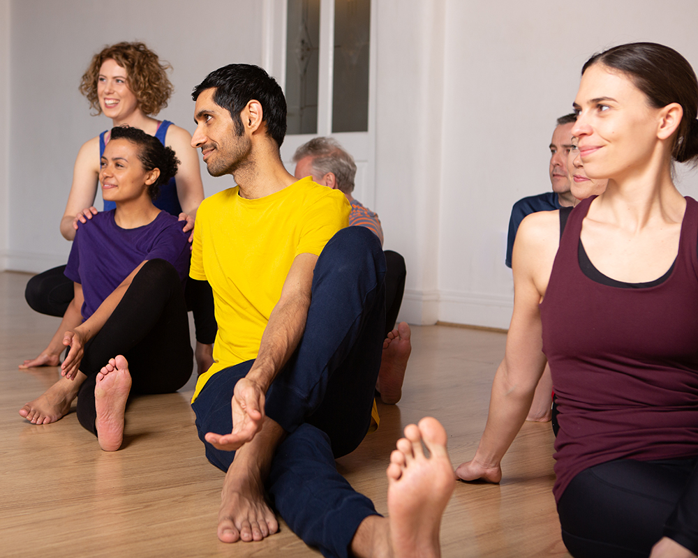 Janine teaches some students a seated twist posture