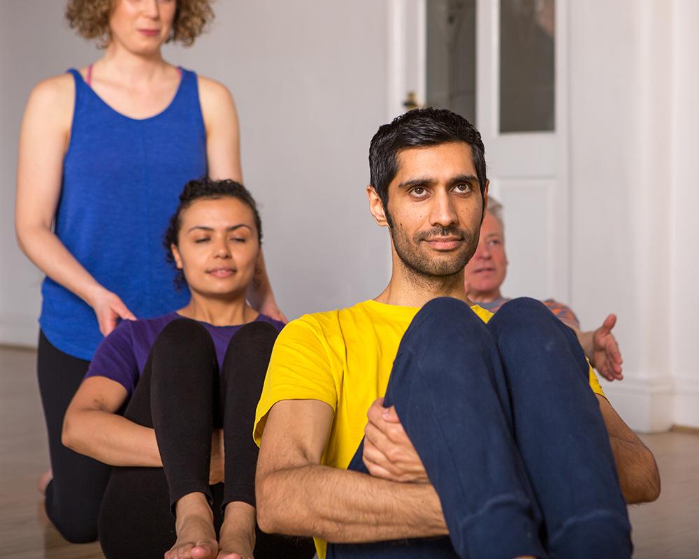 Janine teaches students a balancing yoga posture