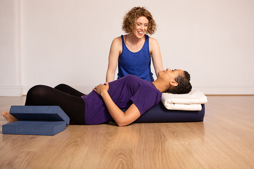 Janine shows a student how to get comfortable in a restorative yoga posture