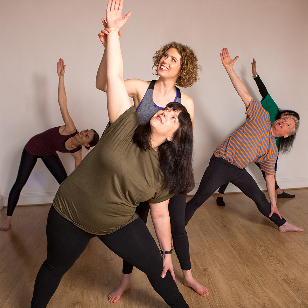 Janine teaches a student triangle pose.
