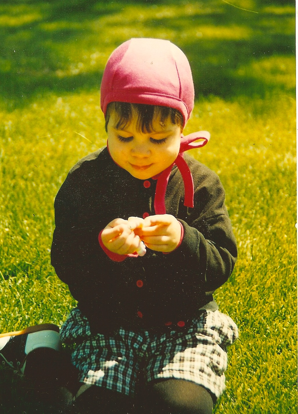 1990 - JoJo . age 2 playing with a walnut, wearing an Earhart Pilot in Size Large - fuscia organic cotton from Spiritex Mills, Asheville, NC. a great US manufacturer of organics. We support!!  Most Age 2 children wear XL, or XXL with revised sizing. Also revised: our ties are thin.