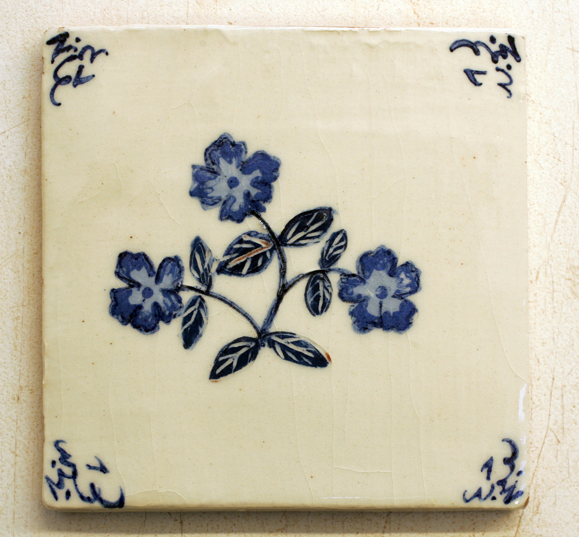 """Our own """" Pops"""" squiggle corner - """"Pops"""" was the nick-name given to the Flanders town of Poperinge in World War I, by the many allied soldiers who enjoyed there a brief respite from the trenches. Much later, Ann saw an old delft tile with an unusual corner design in an antique shop window in Poperinge, and noted it in her sketch book. Our Delft corner tiles are now one of our most popular designs."""