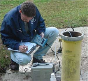 A technician takes a groundwater sample.