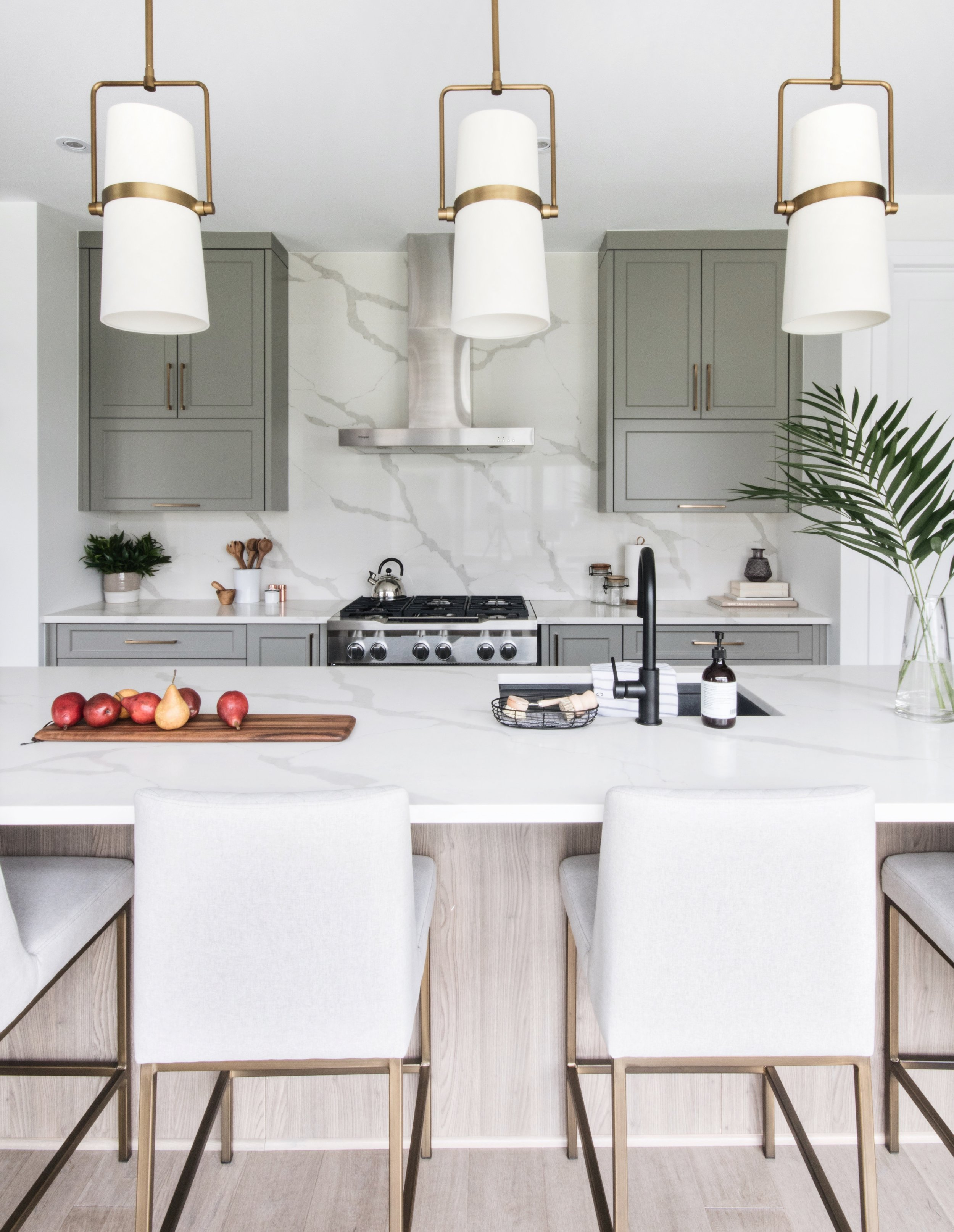 Two-toned kitchen with a laid back California vibe. Flanked on either side by a dramatic patterned tile feature wall and matte black inset cabinets.