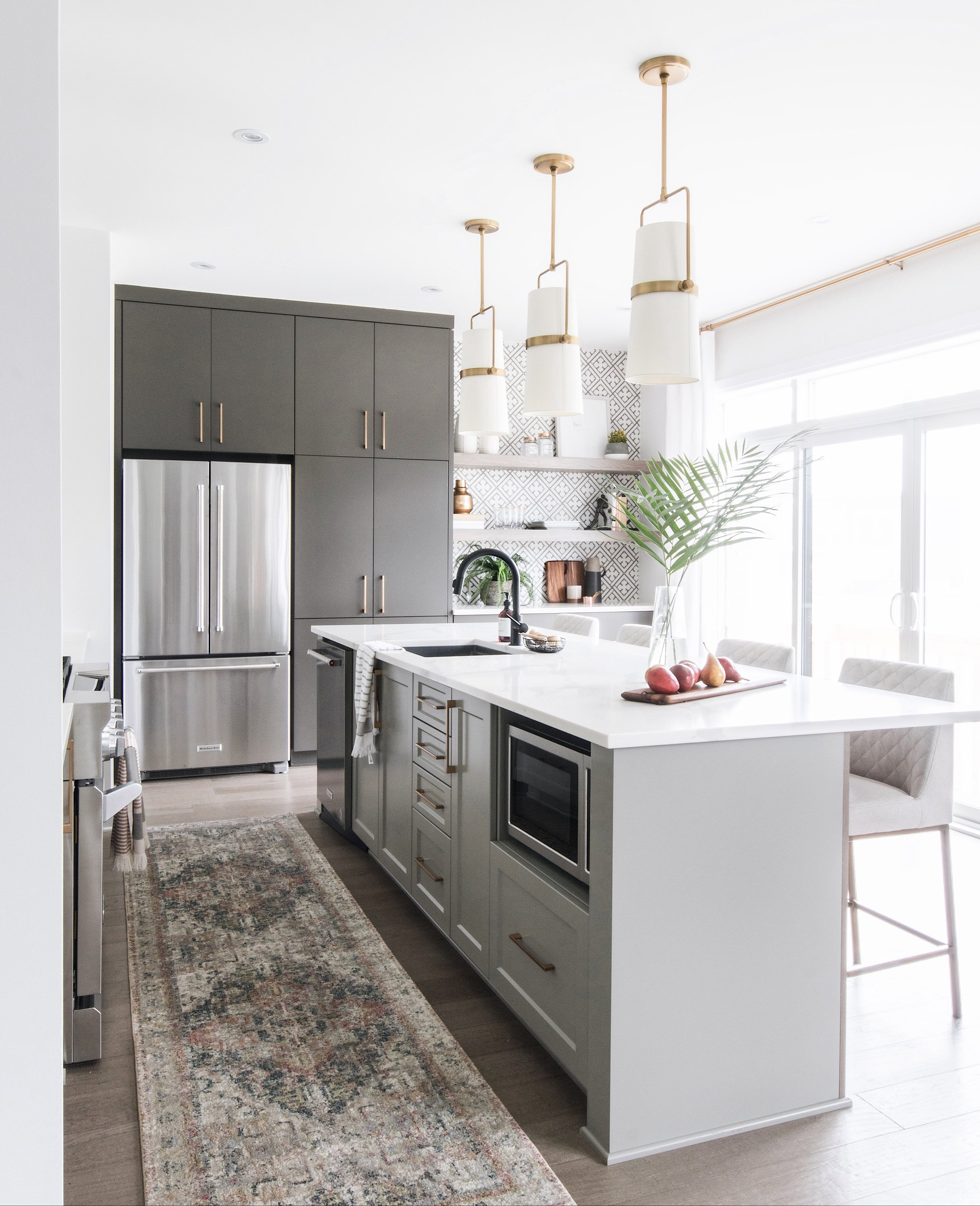 Two-toned kitchen with a laid back California vibe. Flanked on either side by a dramatic patterned tile feature wall and matte black inset cabinets by Ottawa interior design firm Leclair Decor.