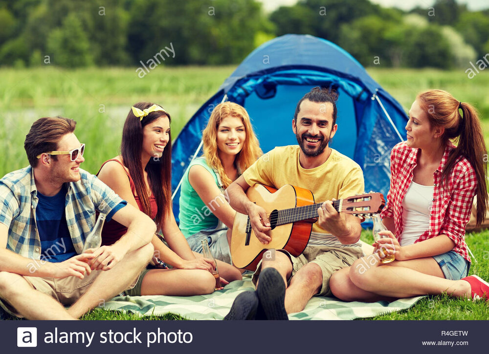 happy-friends-with-drinks-and-guitar-at-camping-R4GETW.jpg