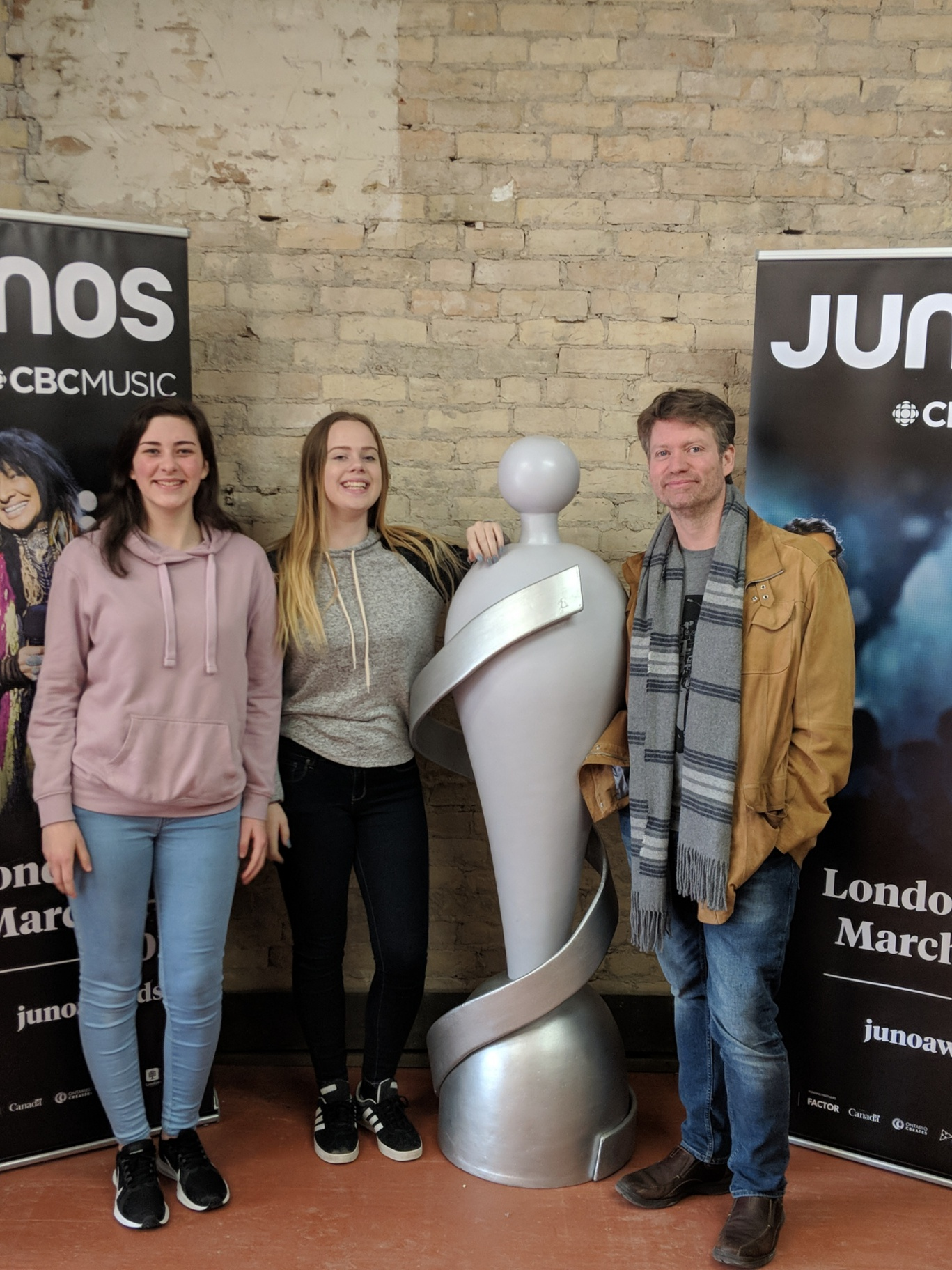 Jenn & Maddie stand in front of Budweiser Gardens in London, where the JUNO Awards will be held on Sunday, March 17th. Second photo: Emily, Jenn & Andrew gather around the life-size JUNO statue that has been added inside JUNO House at 658 Dundas Street in Old East Village in London.