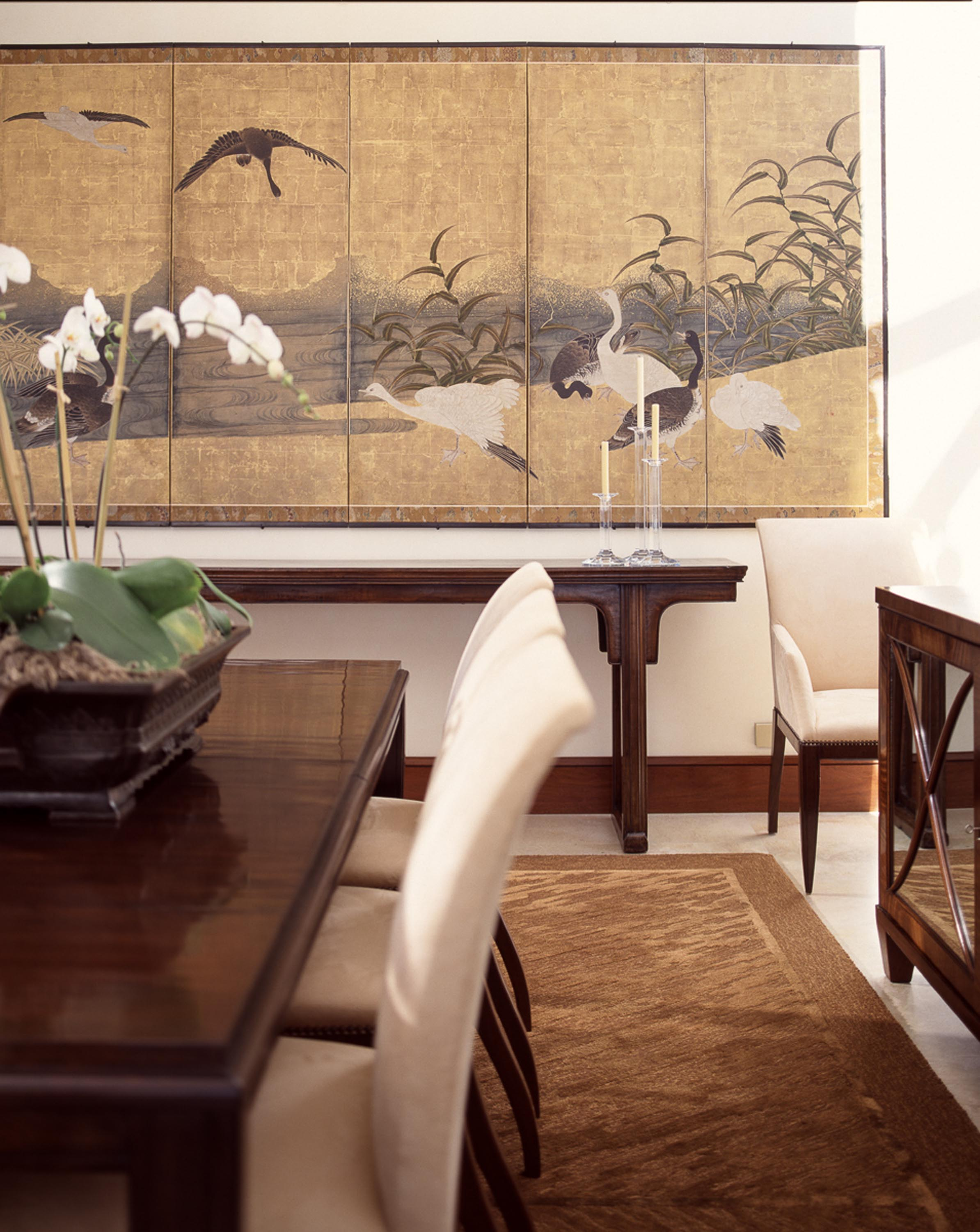 Dining room with wooden table and a plant on top, and frame on wall