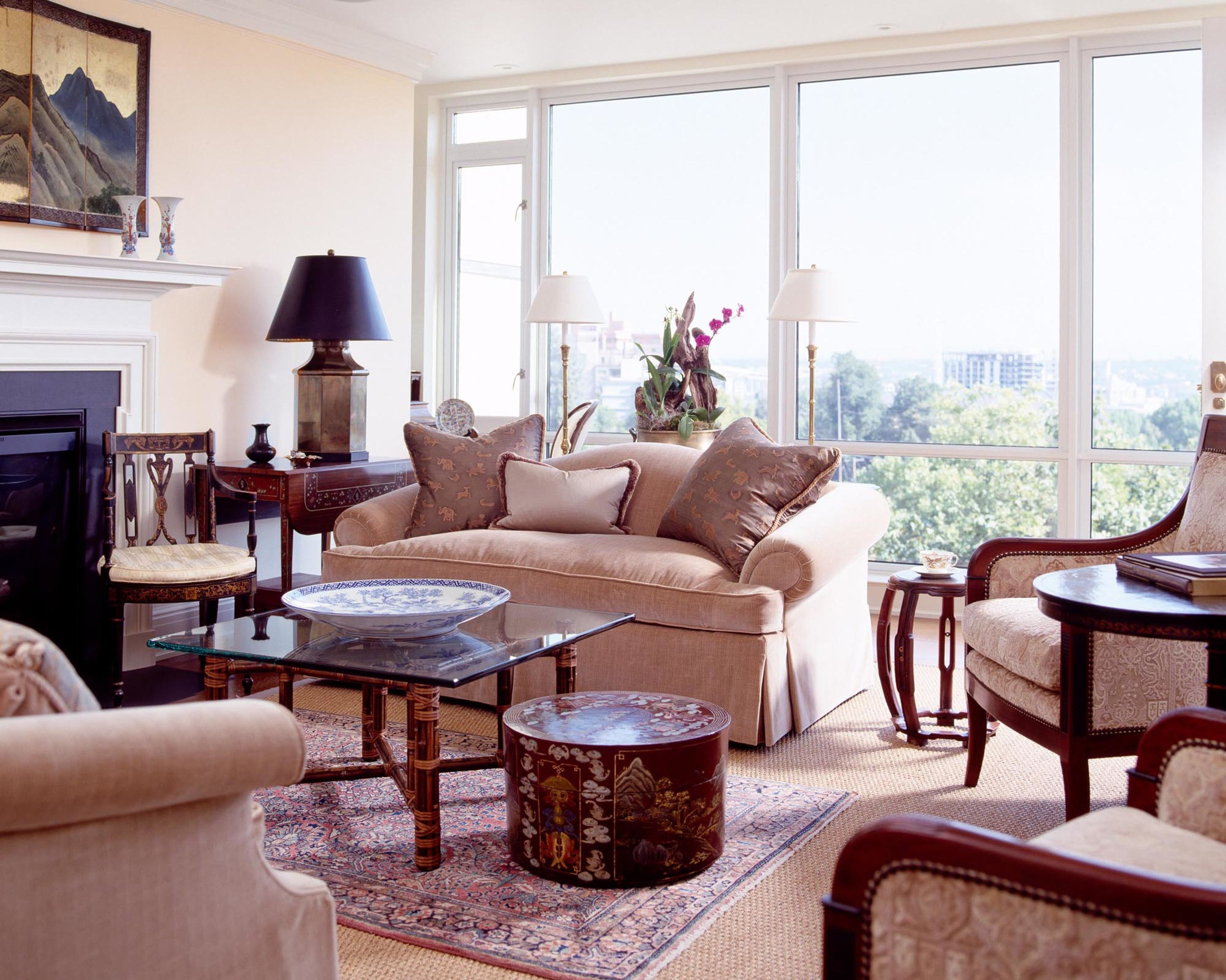 Living room with sofa, armchairs, glass center table, fireplace and a large window
