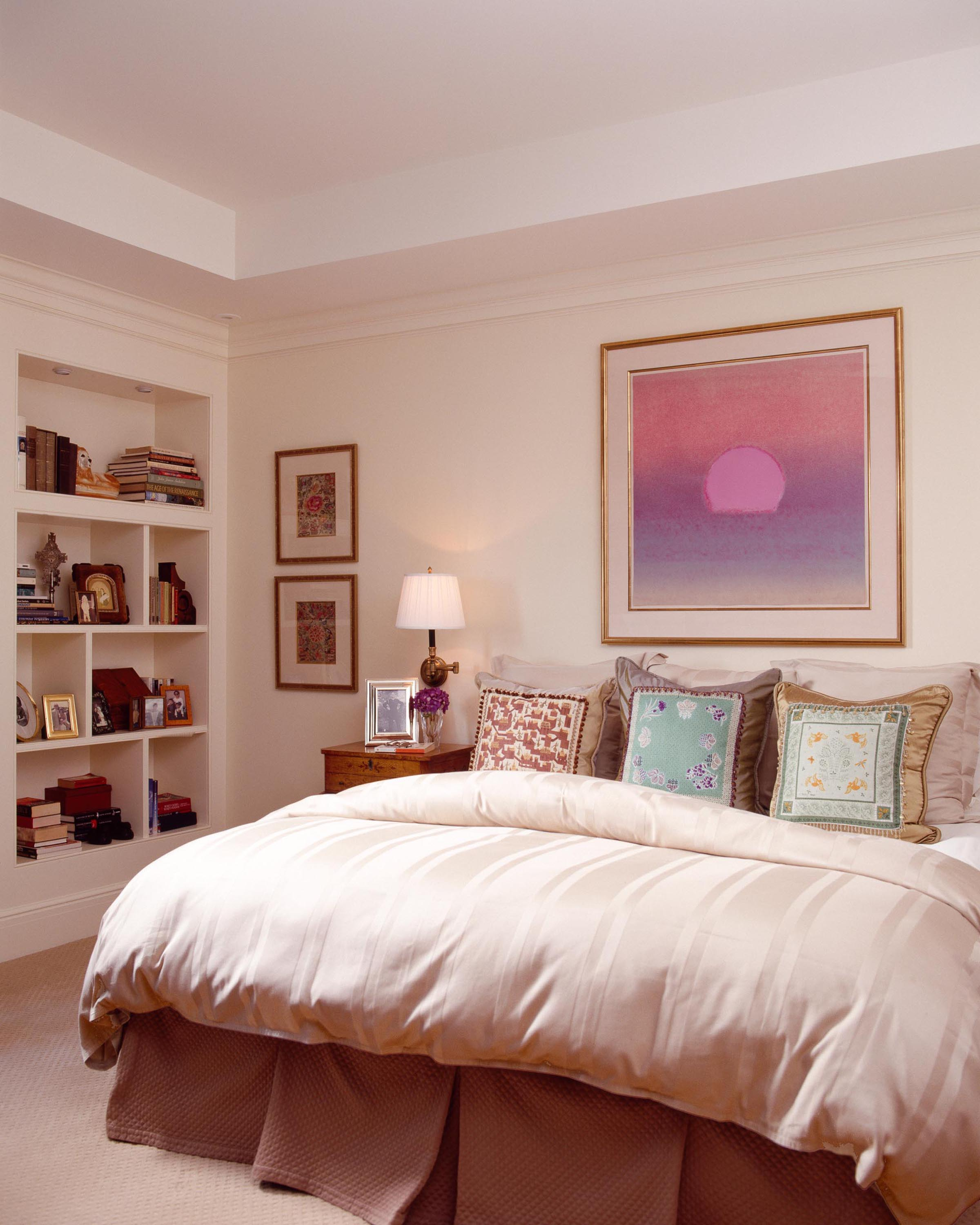 Bedroom with comfortable bed, frames on wall and white shelves with books