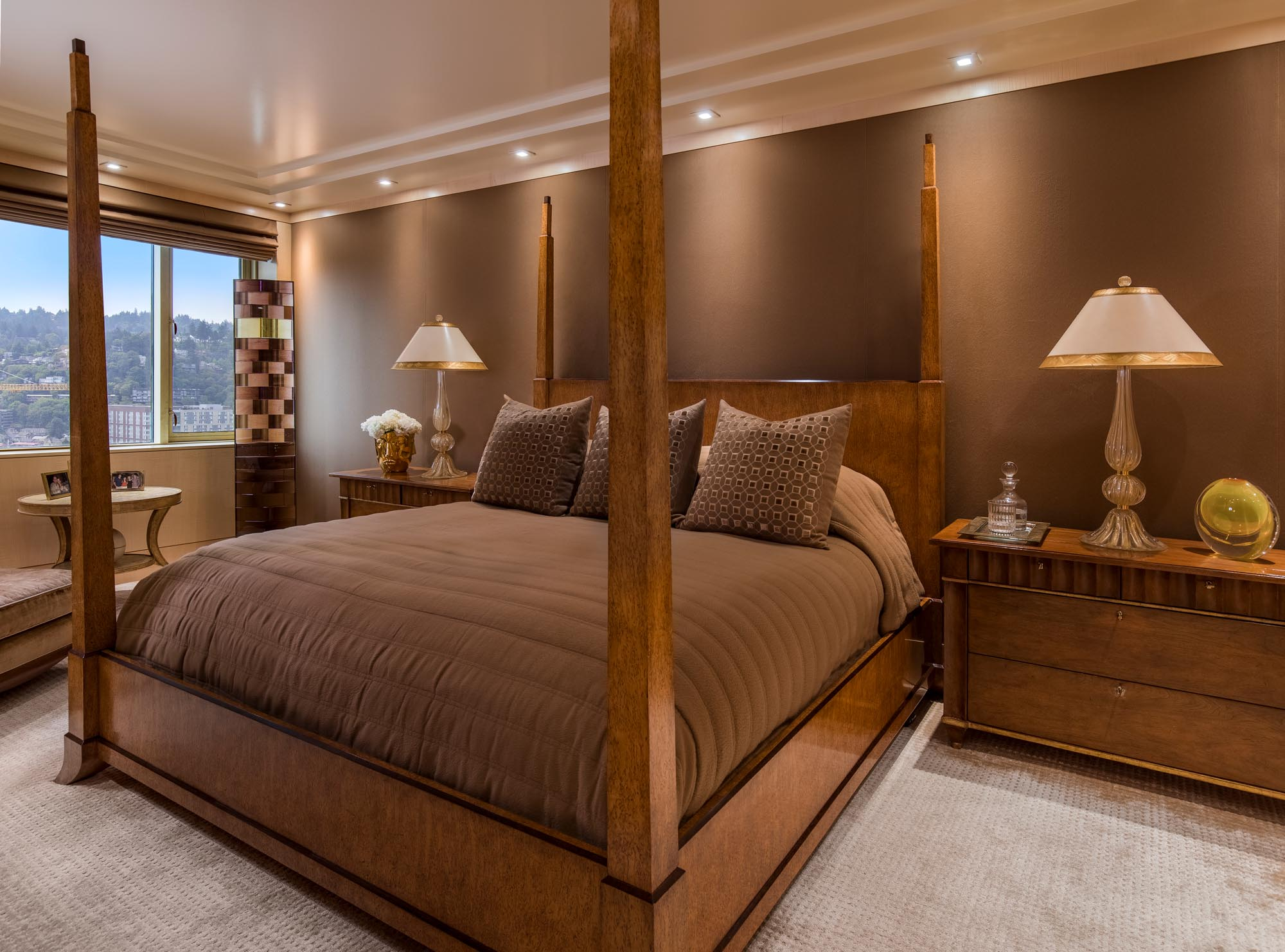 Brown painted wall bedroom with large bed, wooden bed tables and large window