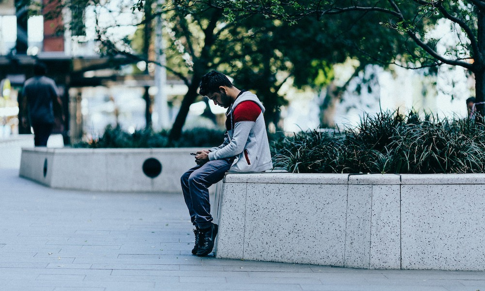 Man-Sitting-on-Wall-Looking-At-Phone.jpg