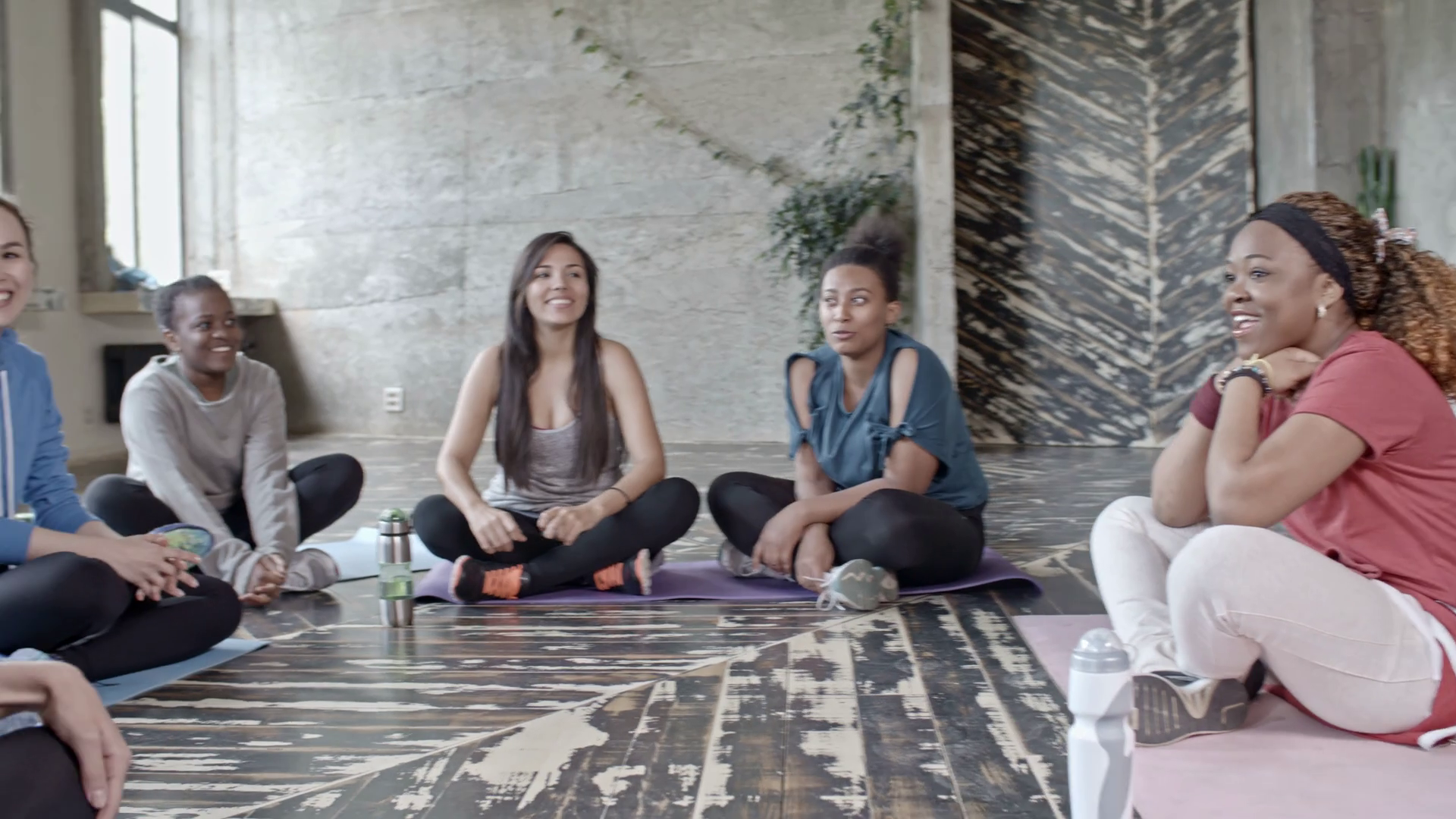 videoblocks-pan-of-curly-young-yoga-instructor-and-multiethnic-group-of-women-sitting-on-mats-in-circle-and-chatting-in-studio-before-class_r8beiu6wz_thumbnail-full01.png