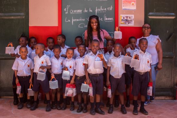 VHF Board Members and children from ISCCH in Haiti with solar powered lights that they received.