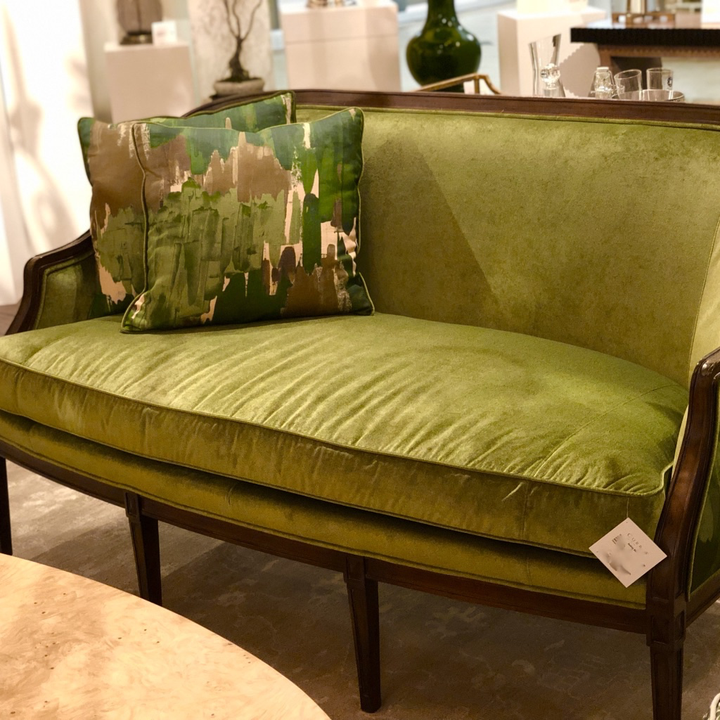 A Currey and Company settee in olive green velvet.