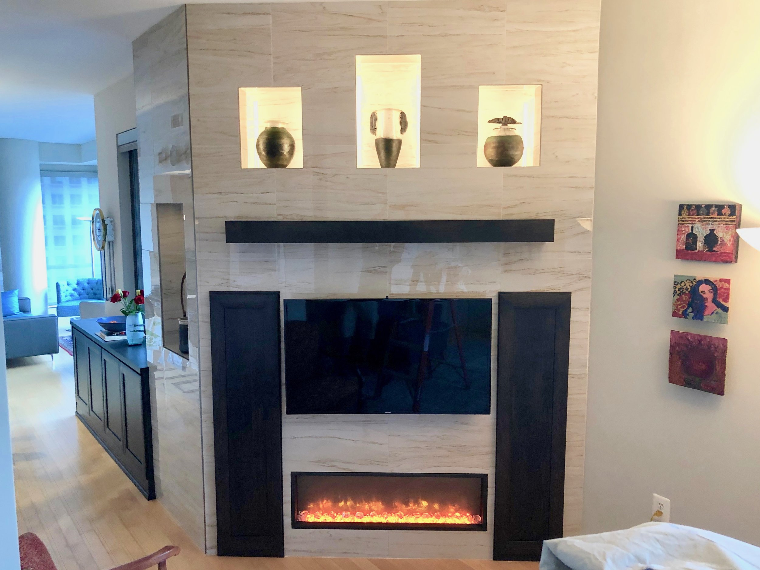 Completed fireplace unit with floating mantle, electric linear fireplace, storage cabinets and three LED lit display niches. To the left you can see the large tiled niche built into the sidewall.