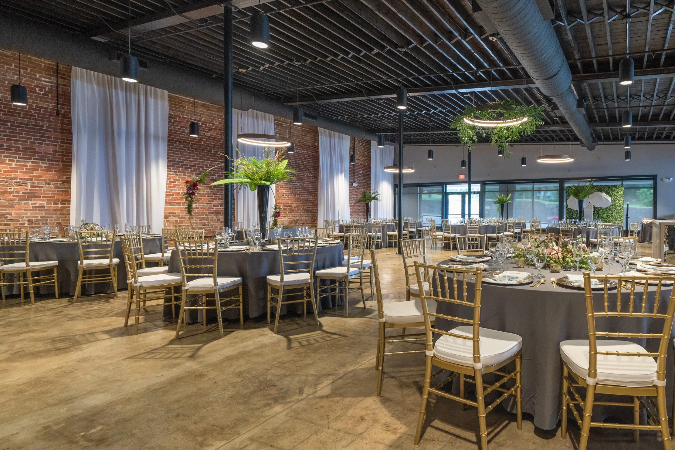 the ballroom - indoor - Featuring brick walls, polished concrete floors, mid-century modern light fixtures, and large windows that let in natural light. The ballroom also features a signature bar with seating.