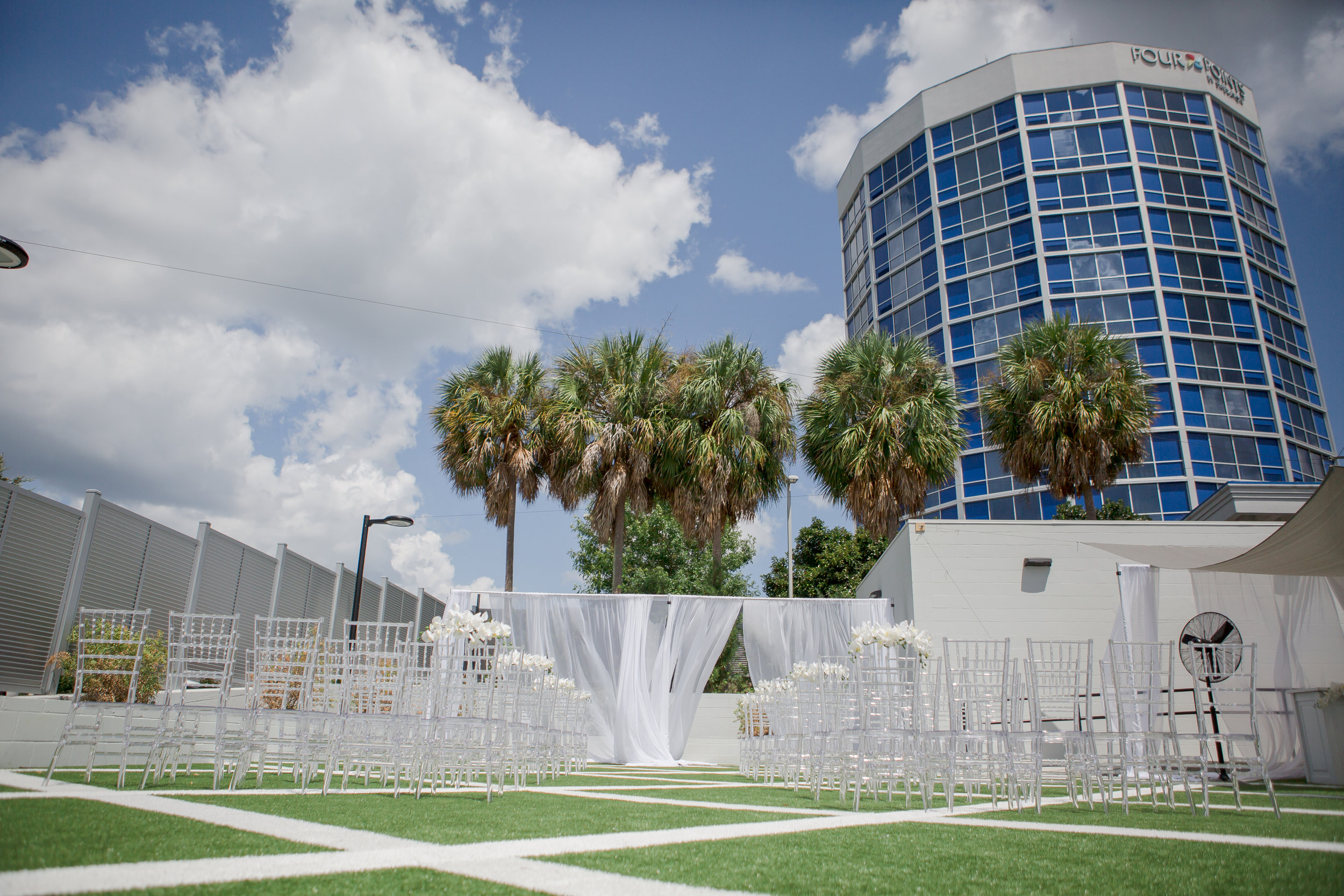 the patio - outdoor - The outdoor patio, located behind the building, features tall privacy fencing and patterned turf flooring. There will also be patio lights draped throughout the space to provide a warm and inviting atmosphere for a variety of events.