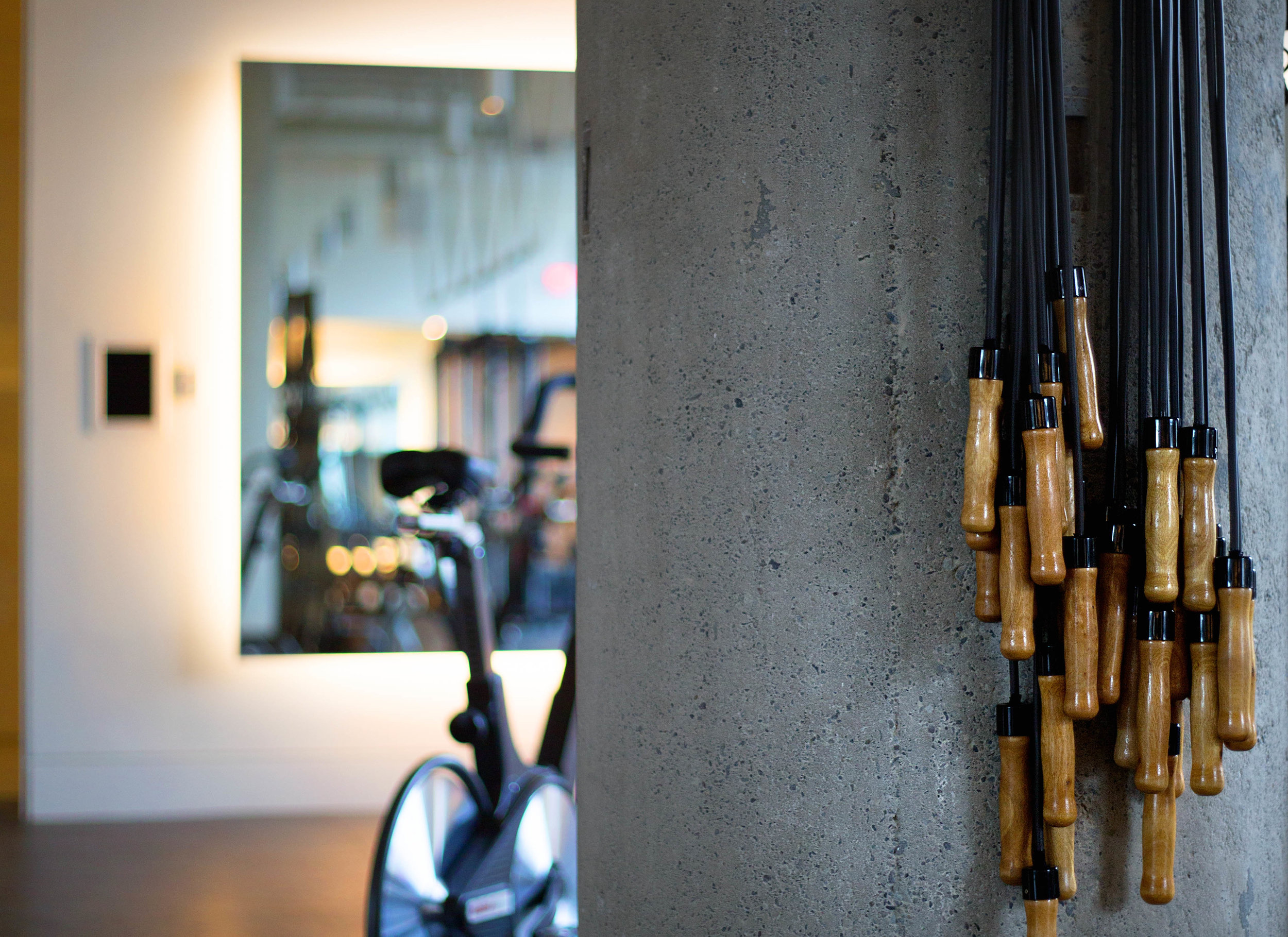 Jump ropes adorn one of the concrete columns within the studio, as natural light sifts across its surface.