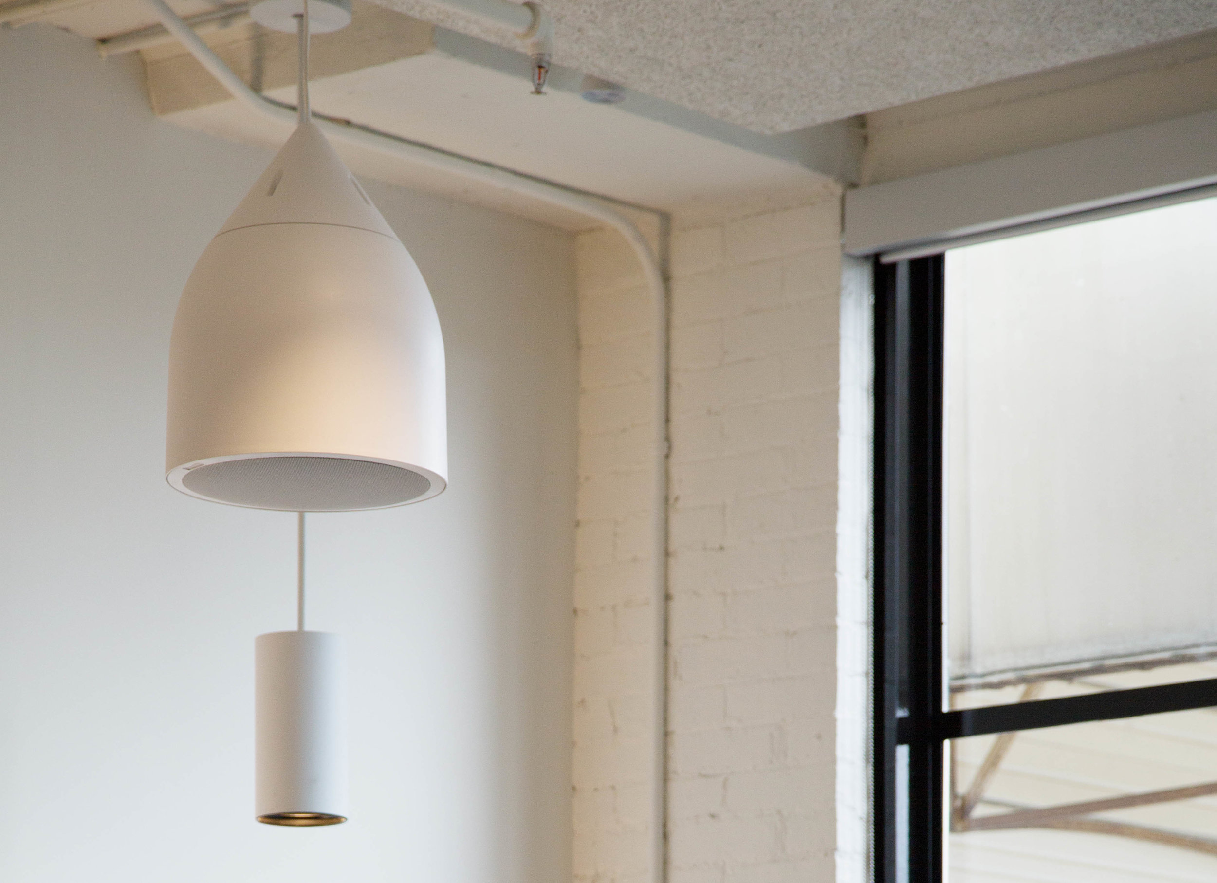 The entirely white ceilings offer both a refined, finished atmosphere, and allow the ample natural light from enormous windows to extend to the depths of the space.