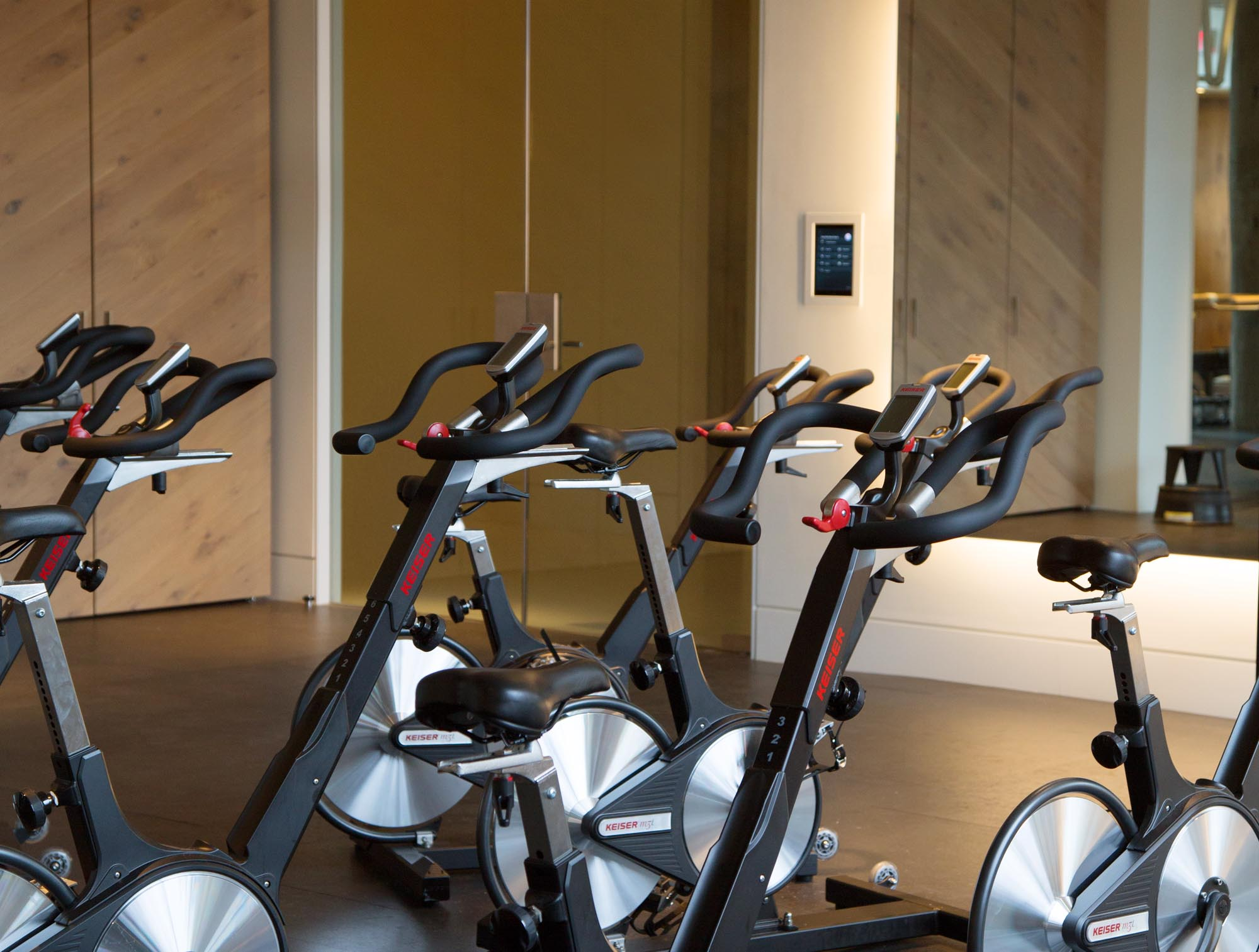The spin cycles sit in front of a large mirrored wall, with the wall-mounted user interface sitting in the background. Anyone who enters the space is welcomed by the iPad, allowing them to setup and enjoy the atmosphere of their choosing.