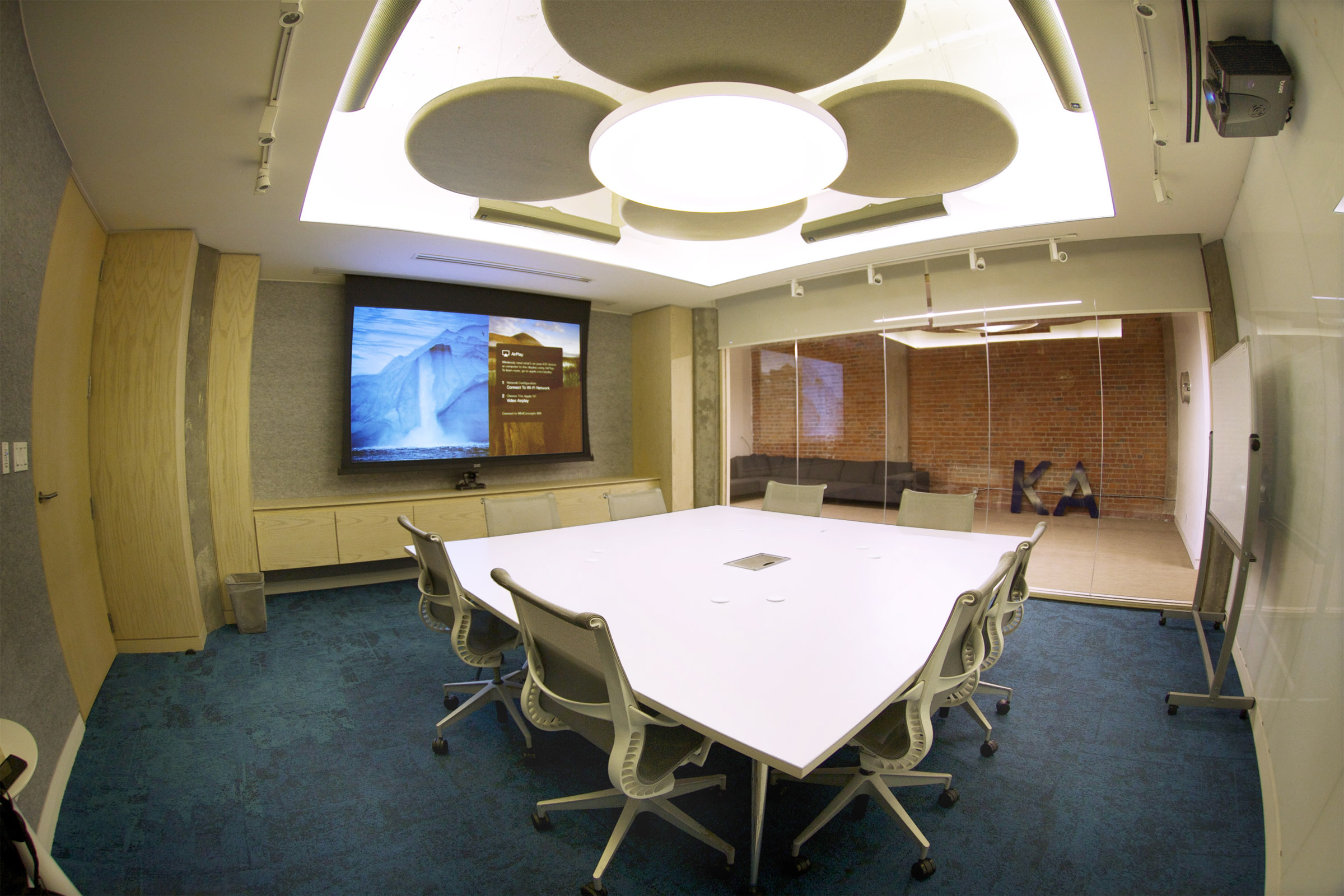 An array of round acoustic panels in an up-lit ceiling cove are surrounded by four Renkus-Heinz speakers.