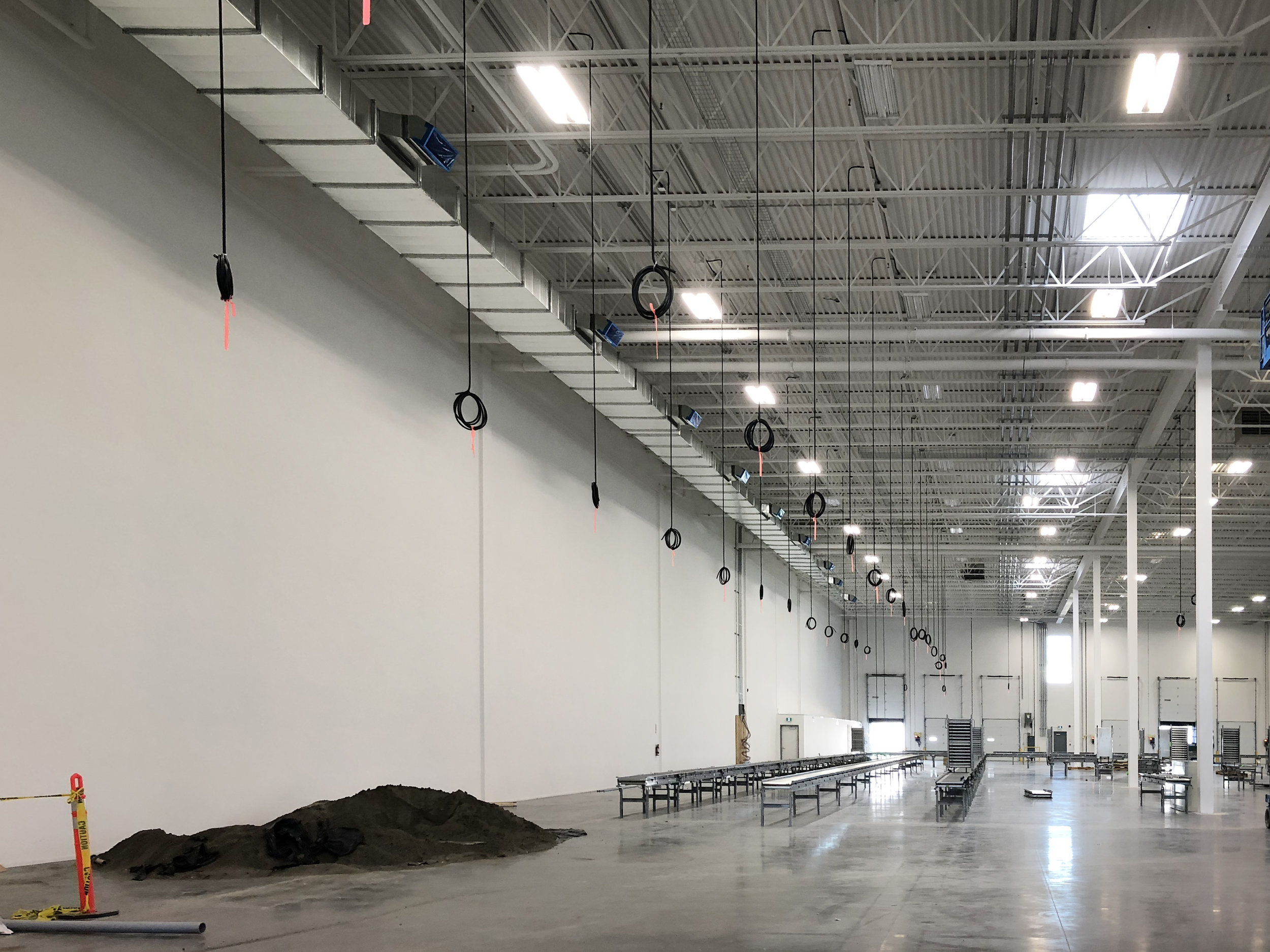In a sorting area that will have many workstations sitting alongside conveyor lines, power cables dangle from the ceiling waiting to be brought down to the desks.