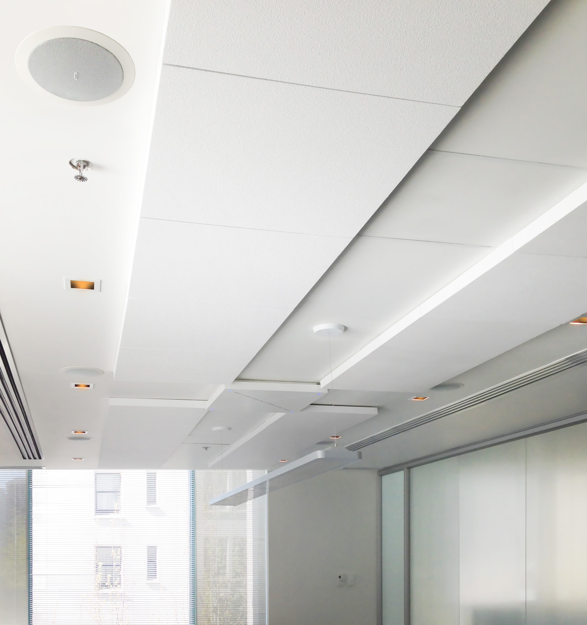 To improve acoustics in this relatively reflective meeting room, we added absorptive acoustic tiling to the ceilings, with a pair of beamforming microphones interleaved within them.