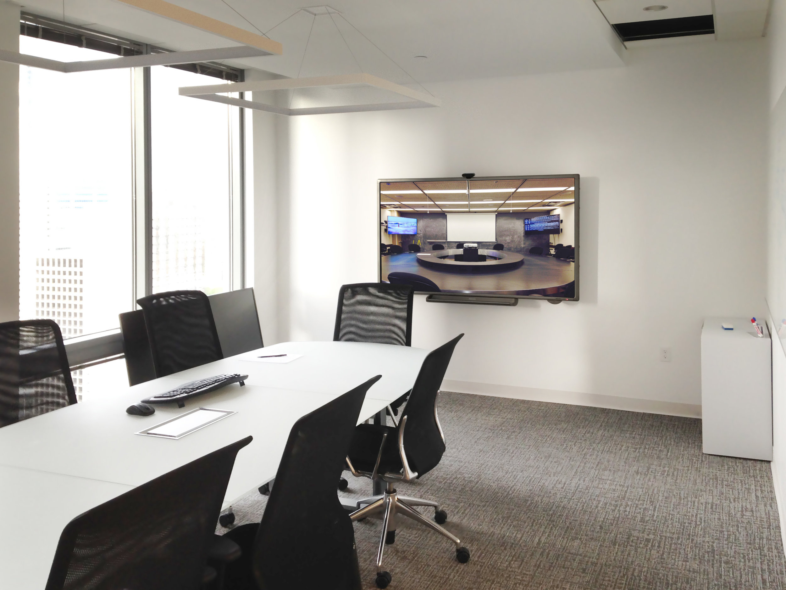 A touch sceen display is connected to a remote room. The DTen interactive display allows users to annotate overtop of an active video conference and it's presented slides to further enhance real time, site-to-site collaboration.