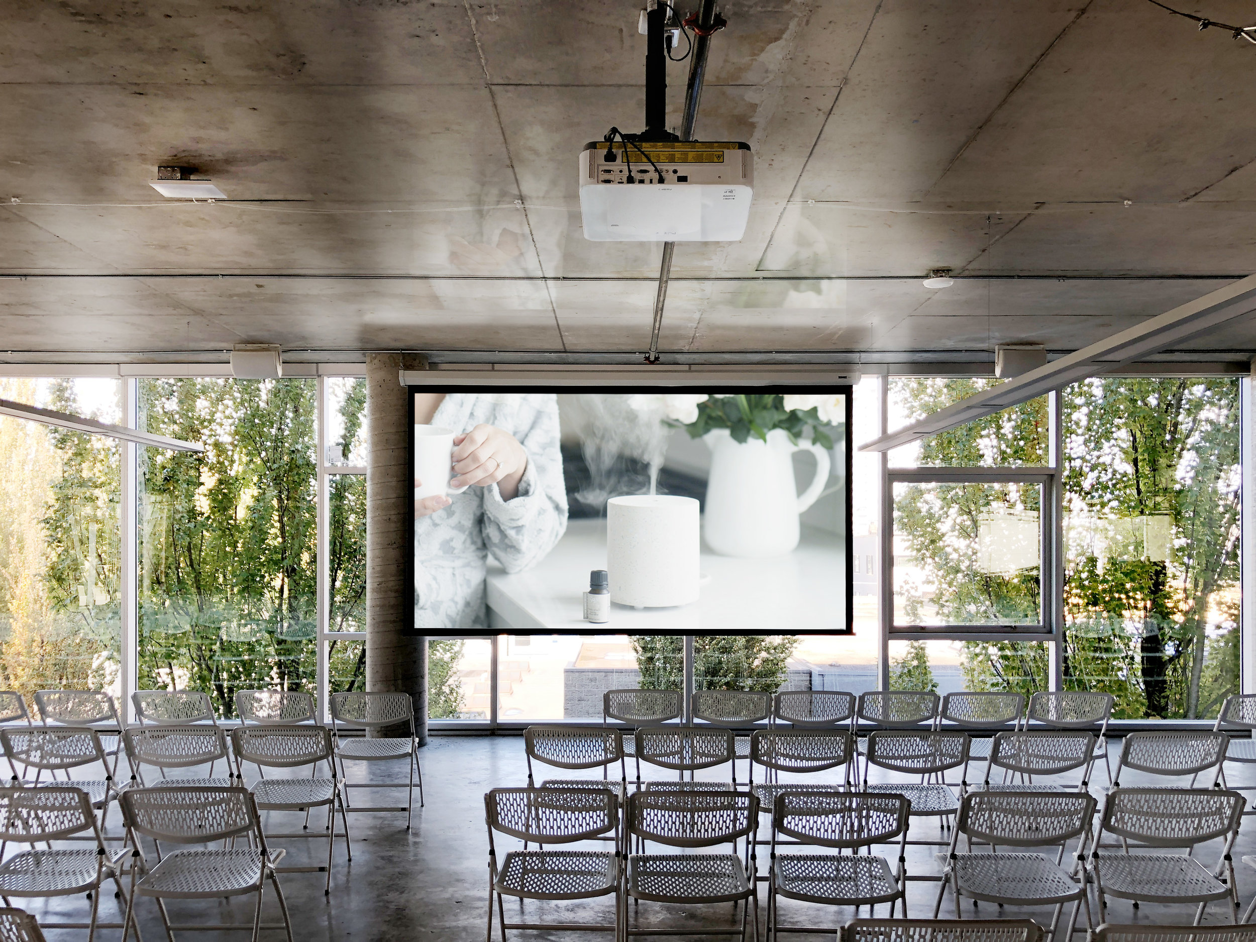 A massive high-gain projection screen with an ambient light reducing surface allows a moderately powerful projector to illuminate an image that can overpower the late day light from in the windows behind it.