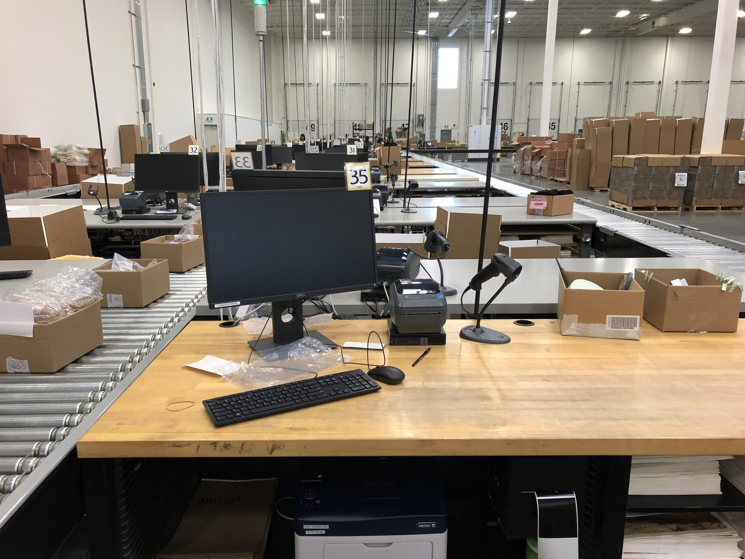 Packing stations where products are pulled from a conveyor, packed up and readied for shipping.