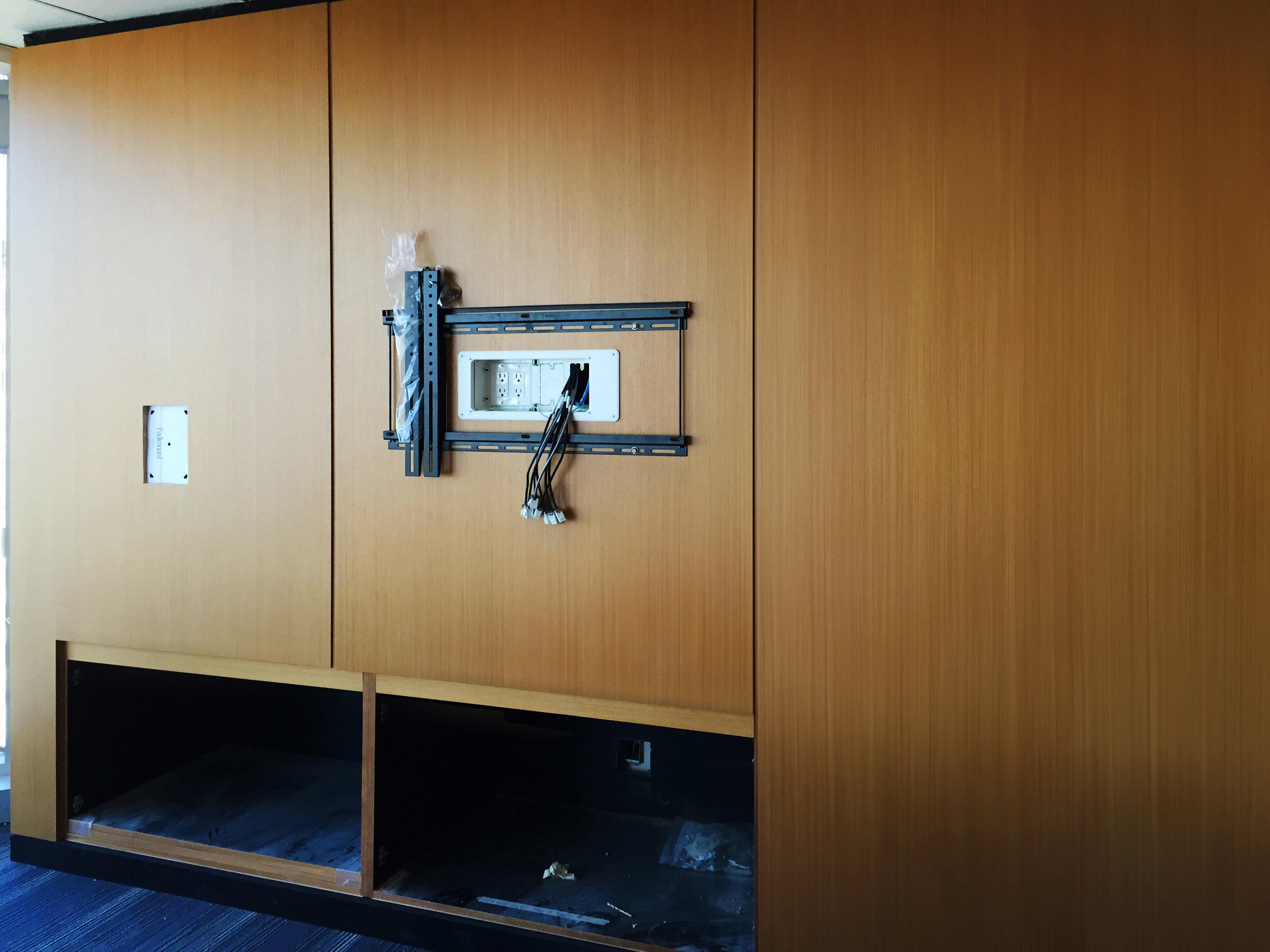 A TV mount is being installed onto the sleek millwork, and an allowance for a control iPad sits at the left, awaiting its hardware.