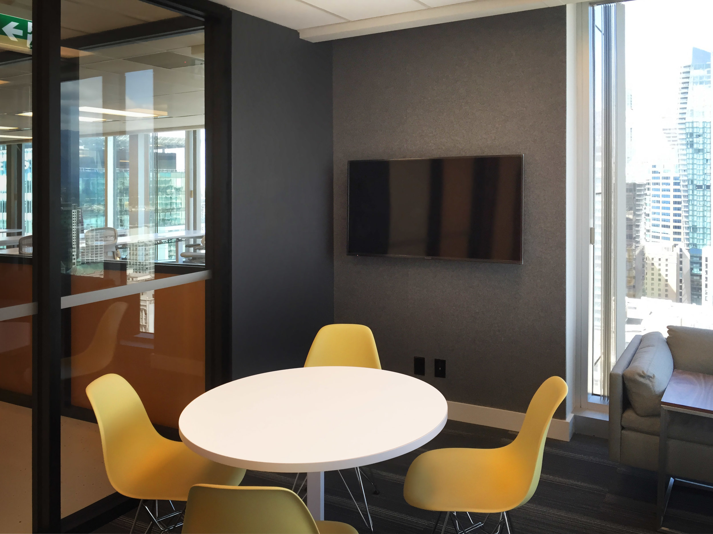 A smaller-sized, enclosed meeting room in the corner of the office, complete with 1960s inspired furniture. The wall behind the TV is clad in felt to help the acoustics in the room. Felt was employed throughout the space to help offset the acoustic reflectivity of the ample glazing.