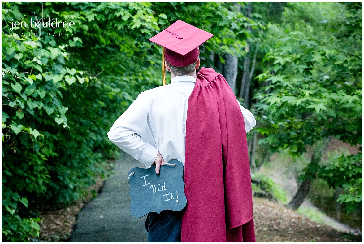 senior guy in cap & gown holding I did it sign.jpg