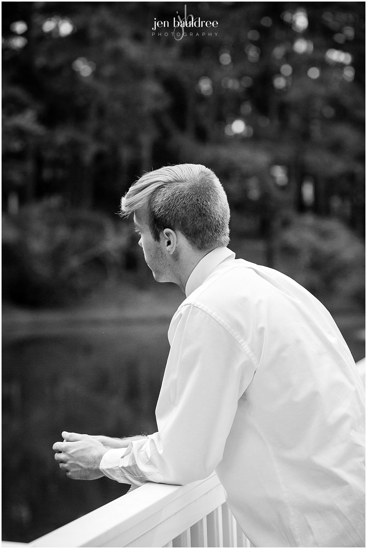 black & white senior portrait guy leaning on railing of dock on pond.jpg