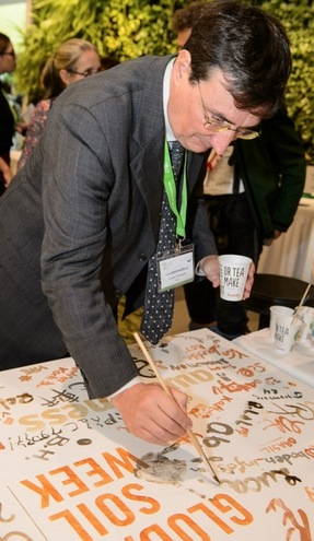 GSBI's Luca Montanarella signs his name on the event banner in soil paint. Photo from Global Soil Week website's    photo gallery   .